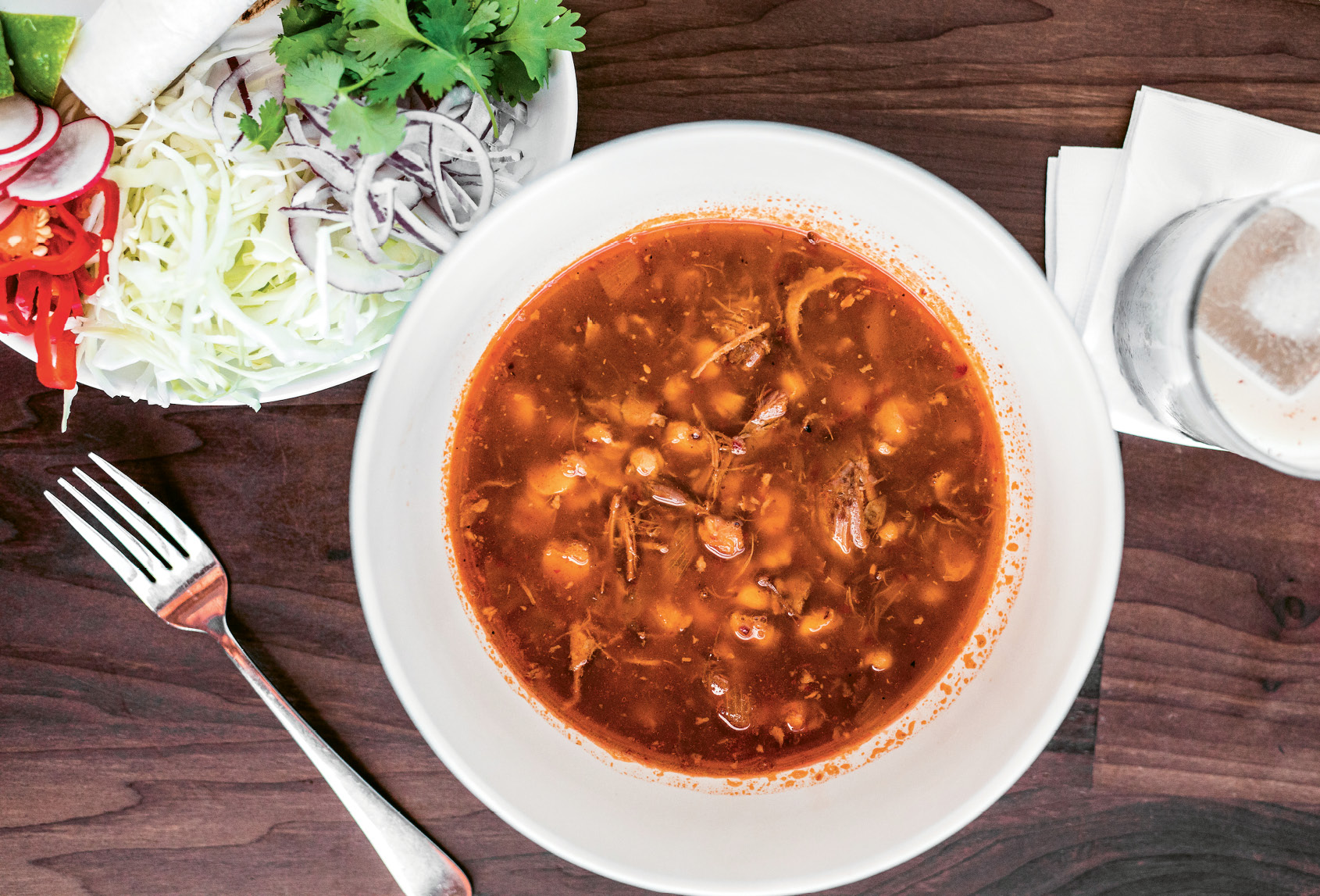 Pozole rojo, a hearty soup with pork shoulder and hominy, awaits fresh toppings.