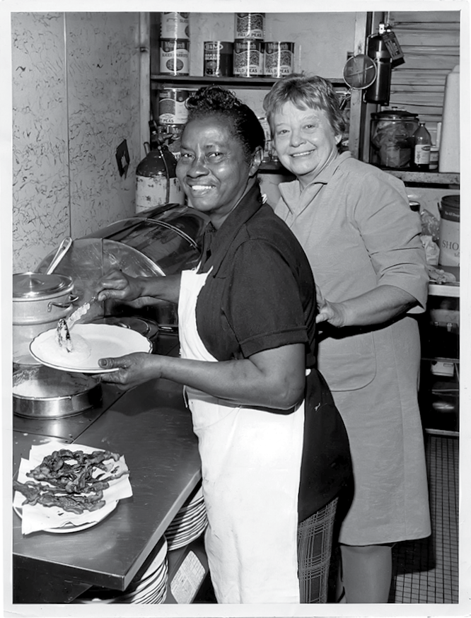 Miss Kitty Proctor dishing up Southern eats with a smile in the 1970s alongside Maddie Heneghen