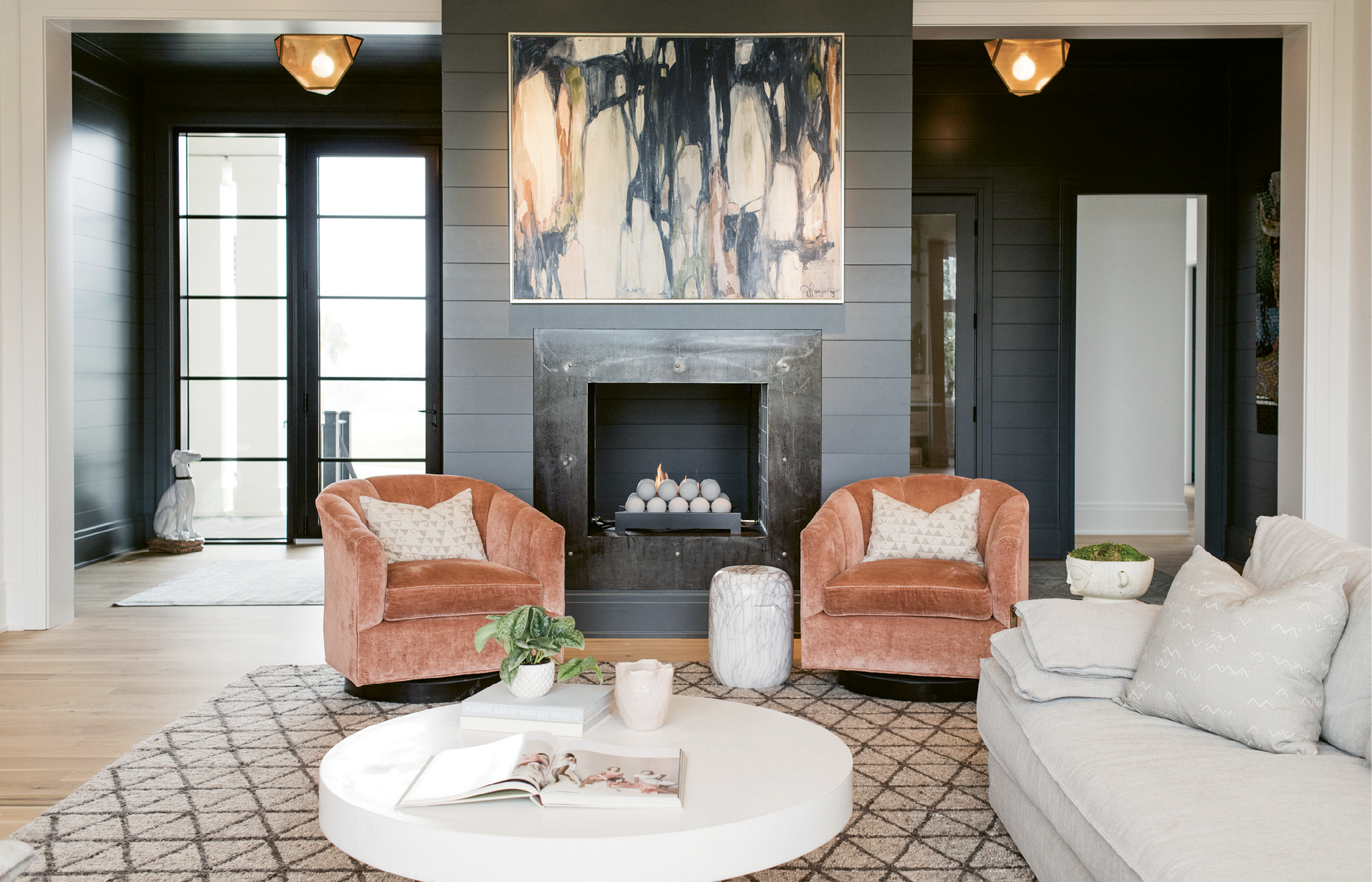The moody foyer, crushed velvet chairs, and abstract painting by Jill Pumpelly add depth to the living room's neutral palette.