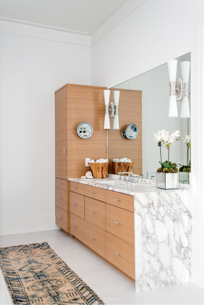 White oak cabinetry and a vintage runner warm the marble-clad master bath. The sconces are from Circa Lighting.