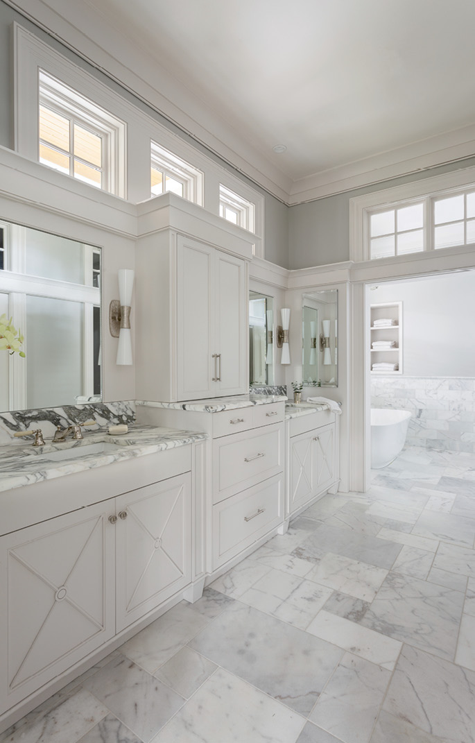 Strategically placed windows in the master bathroom bathe the marble tile in natural light without compromising privacy.