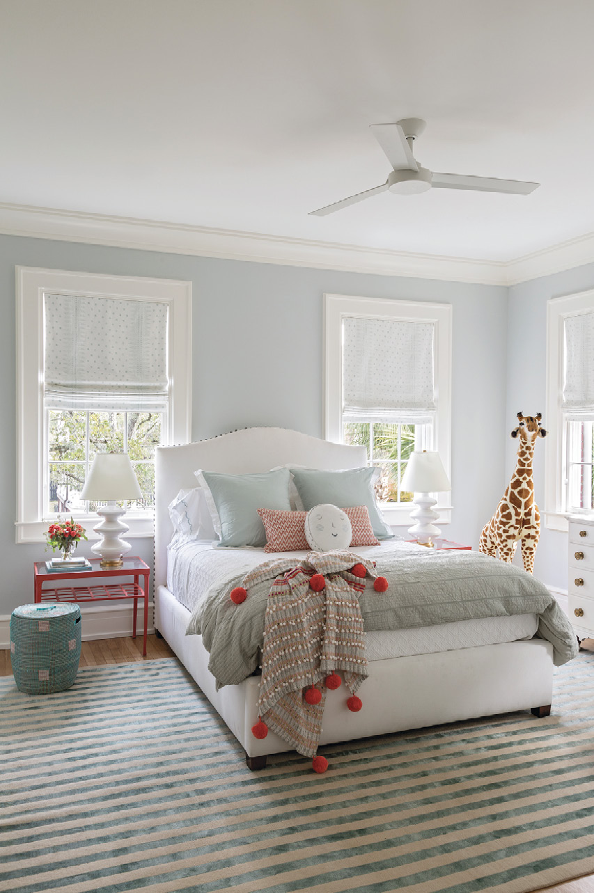 """SWEET DREAMS: The nursery will become a guest room when baby Tucker (whose crib is not pictured) joins his brother in the """"boys' room."""" Dominated by an Elson & Company rug, the space blends elegance and whimsy, from the Benjamin Moore """"Ice Cap"""" paint to the coral bedside tables from Elizabeth Stuart Designs to a friendly stuffed giraffe."""