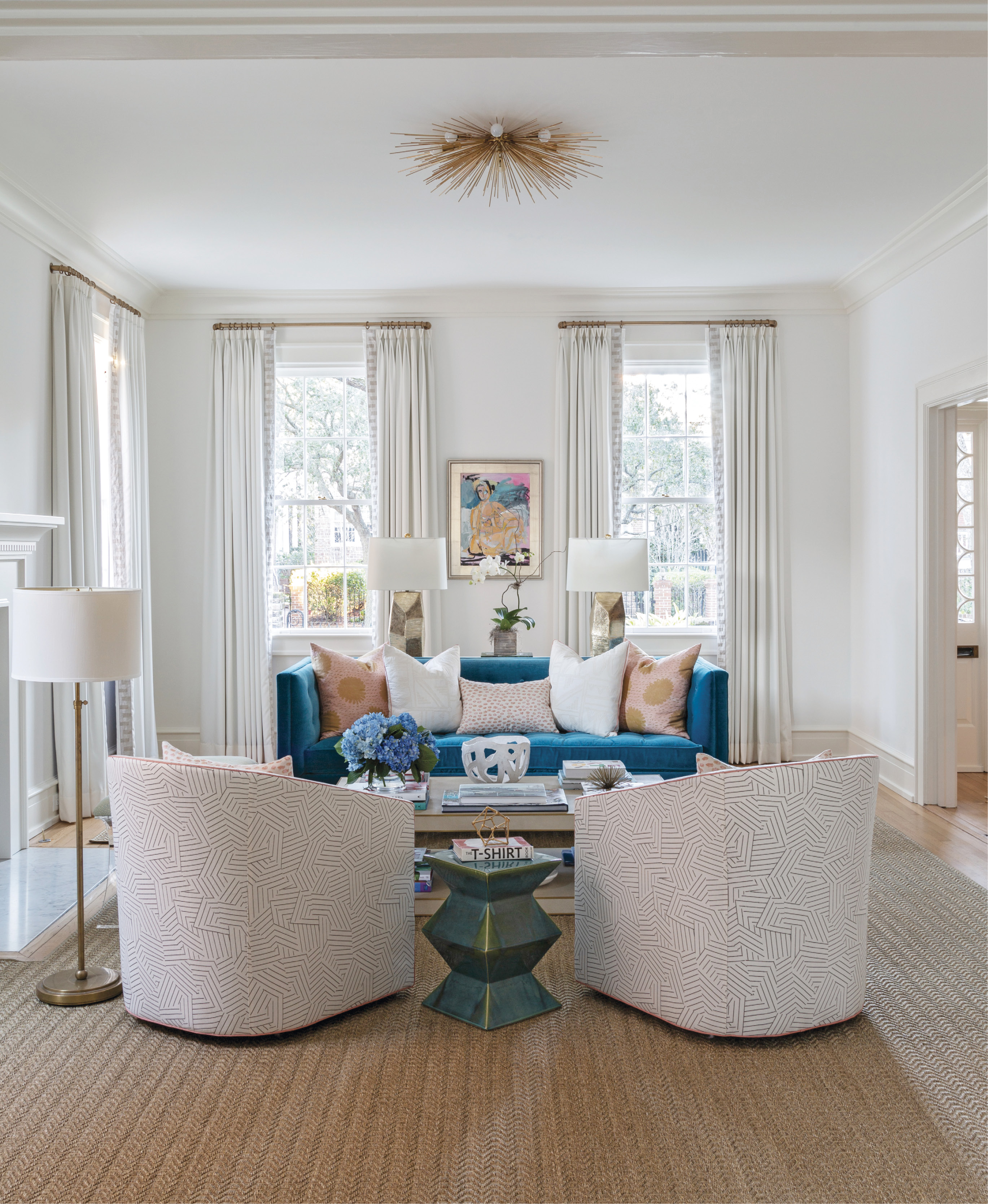 SITTING PRETTY: Cate's art collection set the palettes for the interiors, including this striking figurative work by Anne Darby Parker overlooking a vibrant blue Jonathan Adler velvet sofa and pale blush of the Schumacher fabric-covered club chairs.