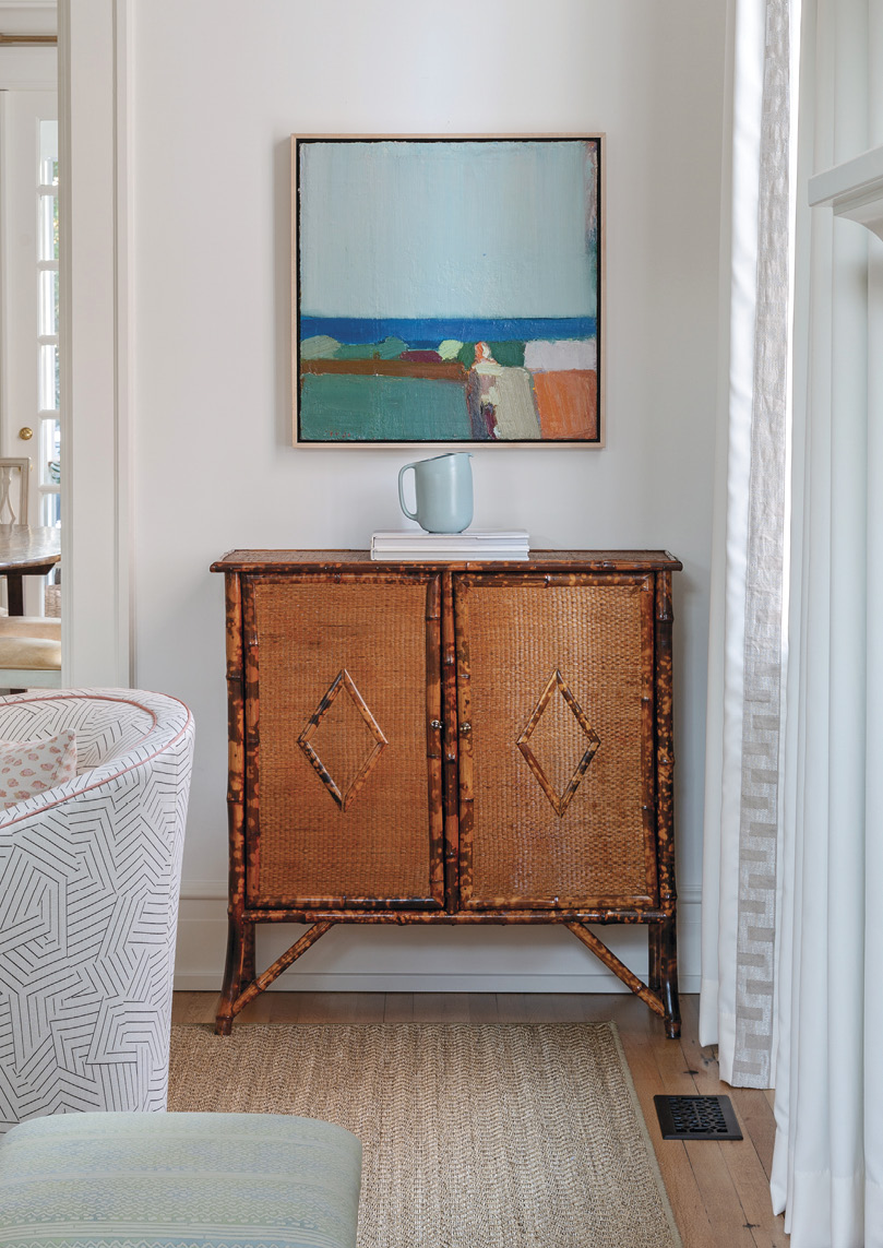 NEUTRAL TERRITORY: Benjamin Moore's 'Simply White' is the backdrop for a mix of natural hues throughout the home, from white oak flooring to a Fibreworks rug, allowing certain pieces to pop, such as this bamboo cabinet from Acquisitions and Sandy Ostrau abstract oil painting from Meyer Vogl Gallery.