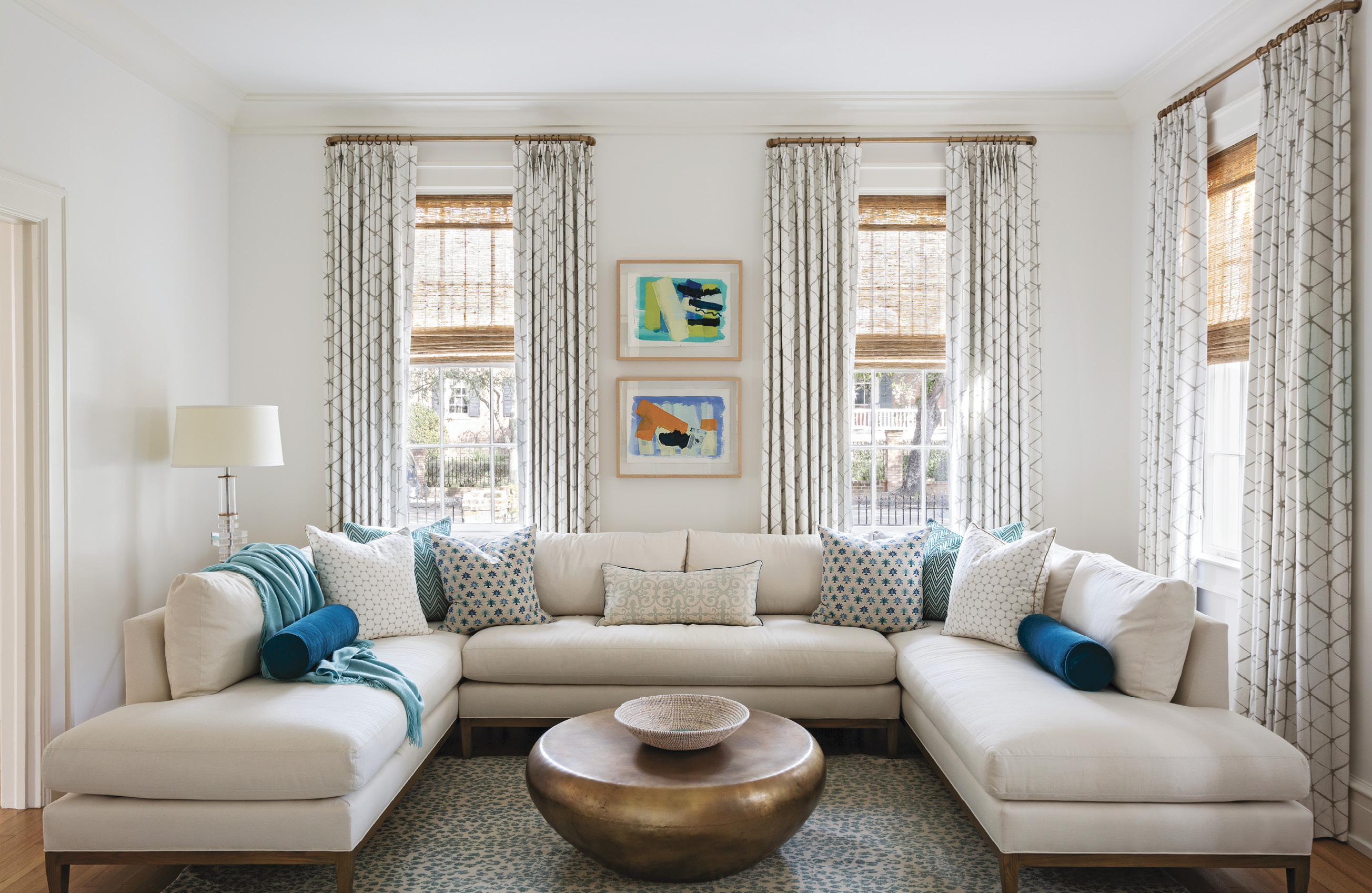 COORDINATED COMFORT: In the laid-back but still stylish family room, a burnt brass-finished cocktail table from Arteriors fills the space in front of the U-shape sectional sofa from Lee Industries. Sally King Benedict paintings, along with scattered throw pillows encased in fabrics from Pierre Frey, Mally Skok Design, and Villa Nova, add color.