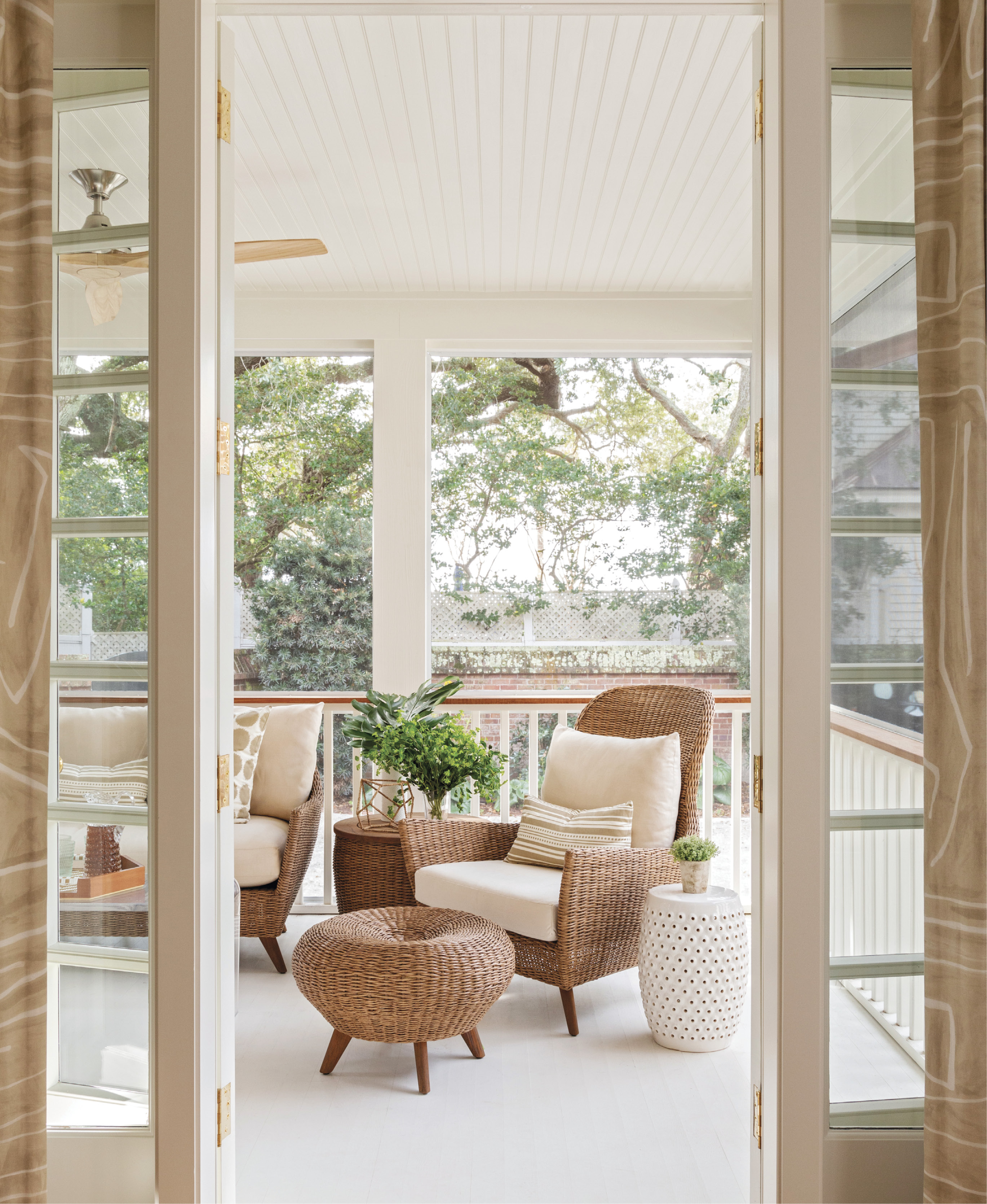 OUTDOORS IN: A glassed-in sun-room was converted into a screened porch to provide more airflow and outdoor space. The Lloyd Flanders sofa from GDC Charleston is often the domain of older Lab, Margot.