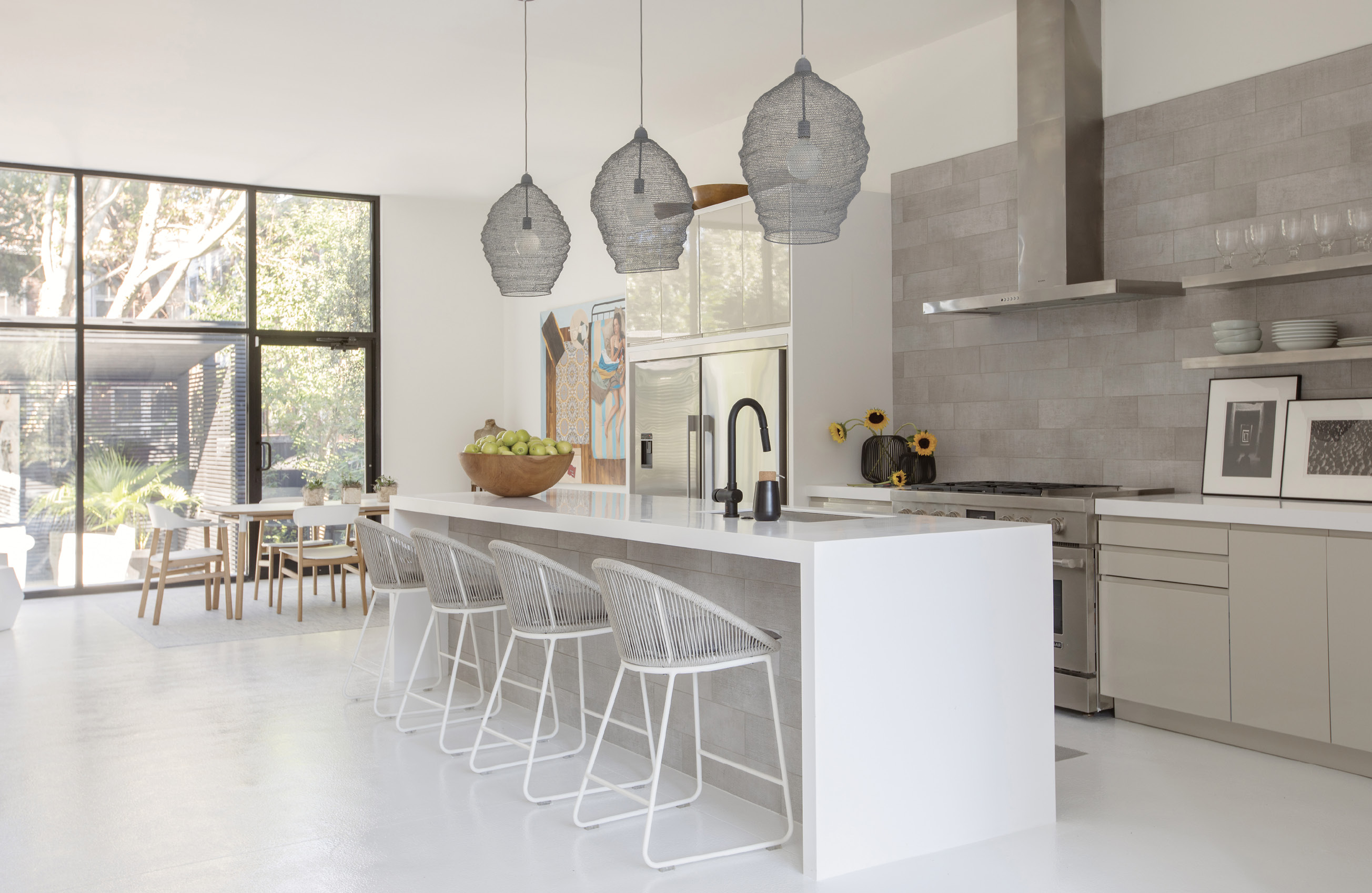 "WHITE SPACE: Mixing textures in white, black, and beige, the kitchen is Baldwin's quiet space. ""With the black exterior and all white interior, I was drawn to a middle ground, and that manifested in a neutral-toned kitchen,"" she says. ""It allows you to have that burst of color as an offset."" Wire pendant lights from Denmark tie in to the industrial feel of the retail-style doors and windows; Teak Warehouse stools complete the look."