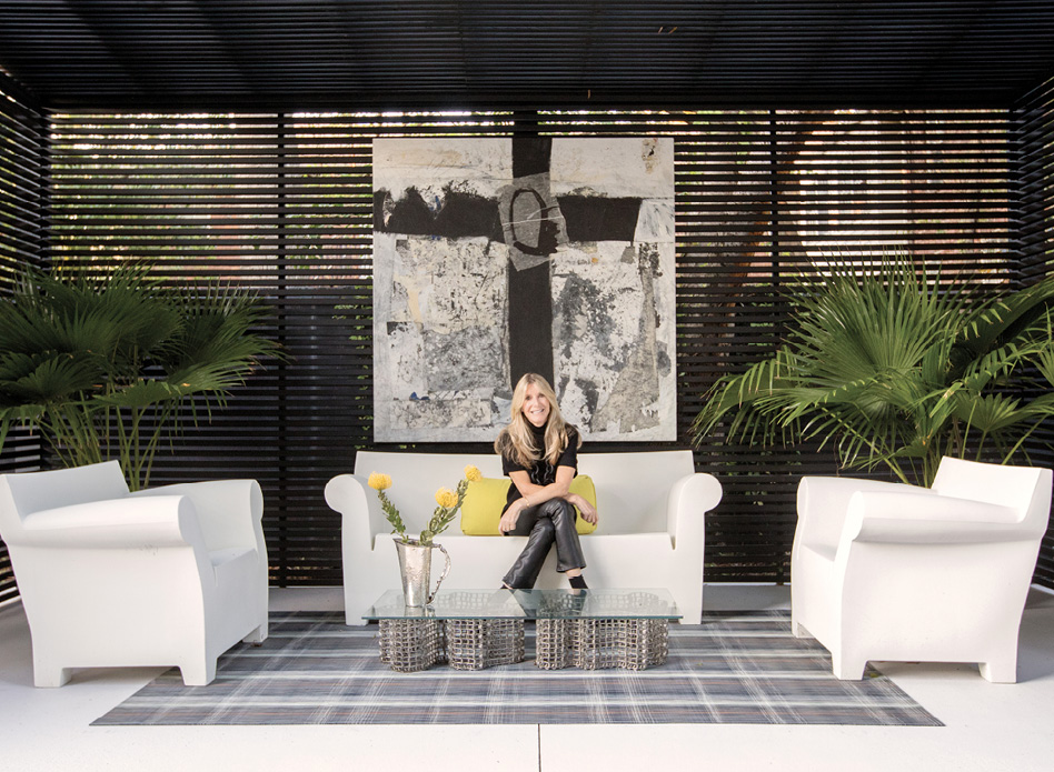Homeowner Karen Baldwin (pictured in the backyard cabana with artwork by Michael Brangoccio) is an avid supporter of Charleston's contemporary art scene.