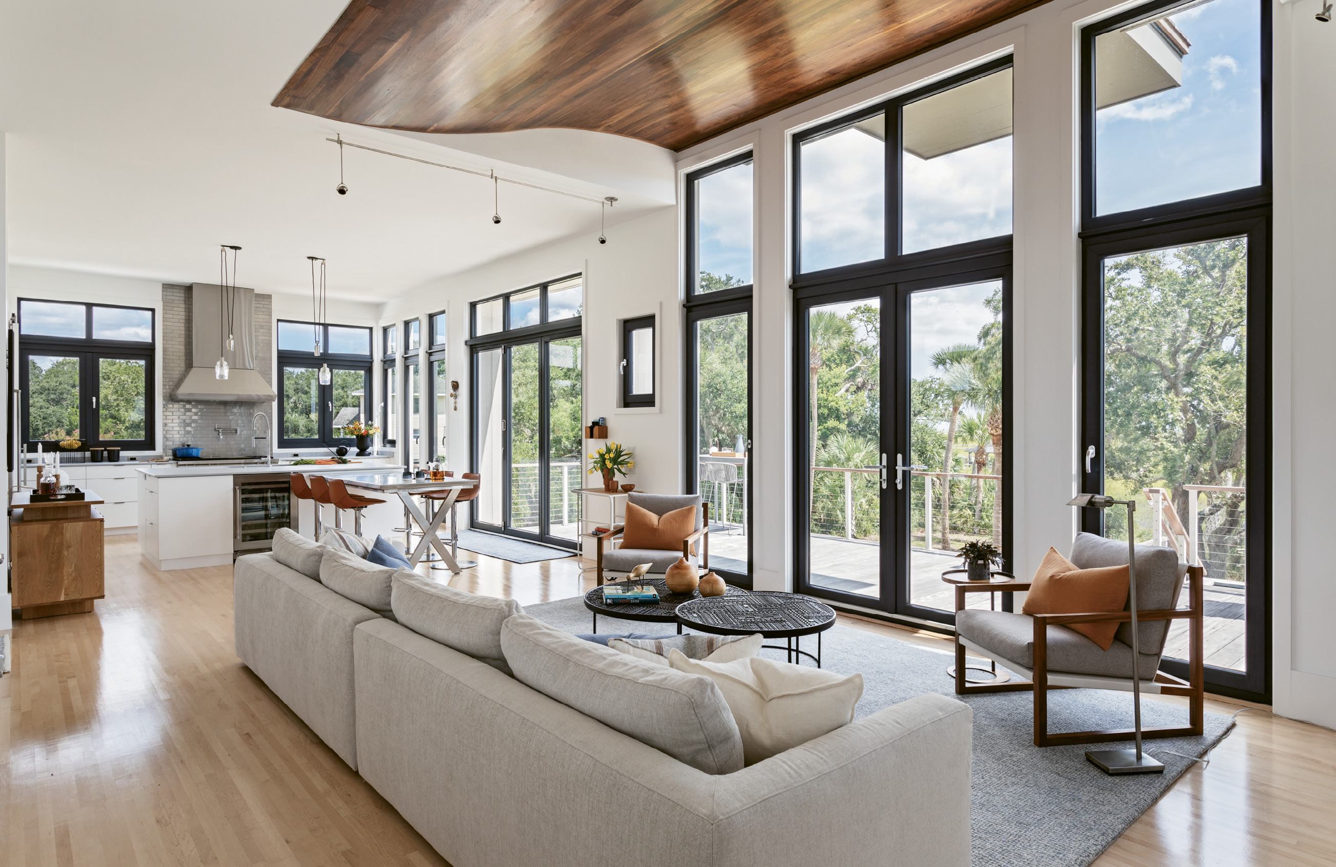 LINES OF SIGHT: Custom Henselstone German windows and glass doors open out from the main living space onto a spacious deck. In the elongated lounge area, low-slung contemporary European furniture with unobtrusive styling helps keep the focus on the outdoors.