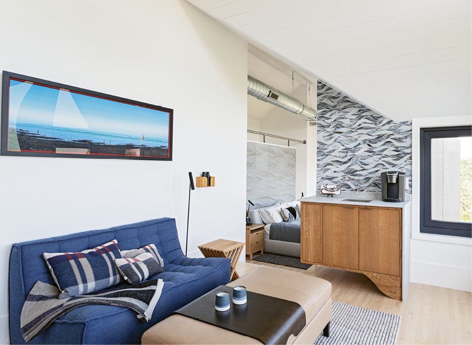 """The """"observatory"""" features a bright blue sofa, the perfect spot to relax with a cup of coffee from the curvaceous oak bar with its ocean-inspired tile backsplash."""