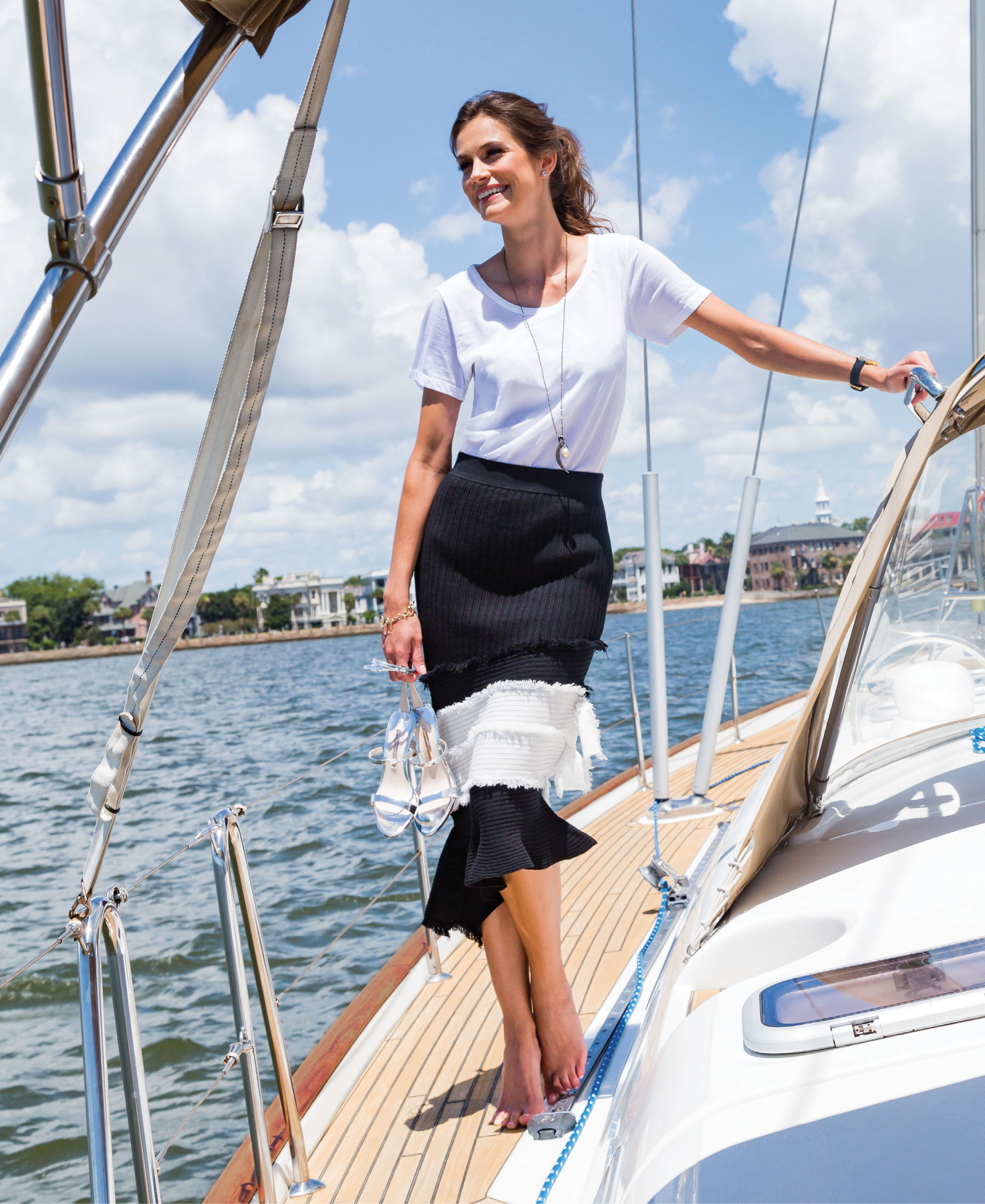 """Majestic Filatures short sleeve top in white, $120 at Gwynn's of Mount Pleasant; Jonathan Simkhai """"Ribbed Bandage Midi Skirt,"""" $395 at Berlin's for Women; Sophia Webster metallic leather """"Rosalind Crystal"""" sandal in """"silver,"""" $495 at Gwynn's of Mount Pleasant and Shoes on King; Rebeka Hakimi 14K white-gold, topaz, and diamond earrings, $420 at Diamonds Direct; Forever Creations USA pavé diamonds and pearl on pyrite pendant necklace, $250 at Out of Hand; 14K yellow-gold link bracelet, $1,150 at Polly's Fine Jewelry; Berg + Betts """"The Classic"""" watch, $128 at Maris DeHart"""
