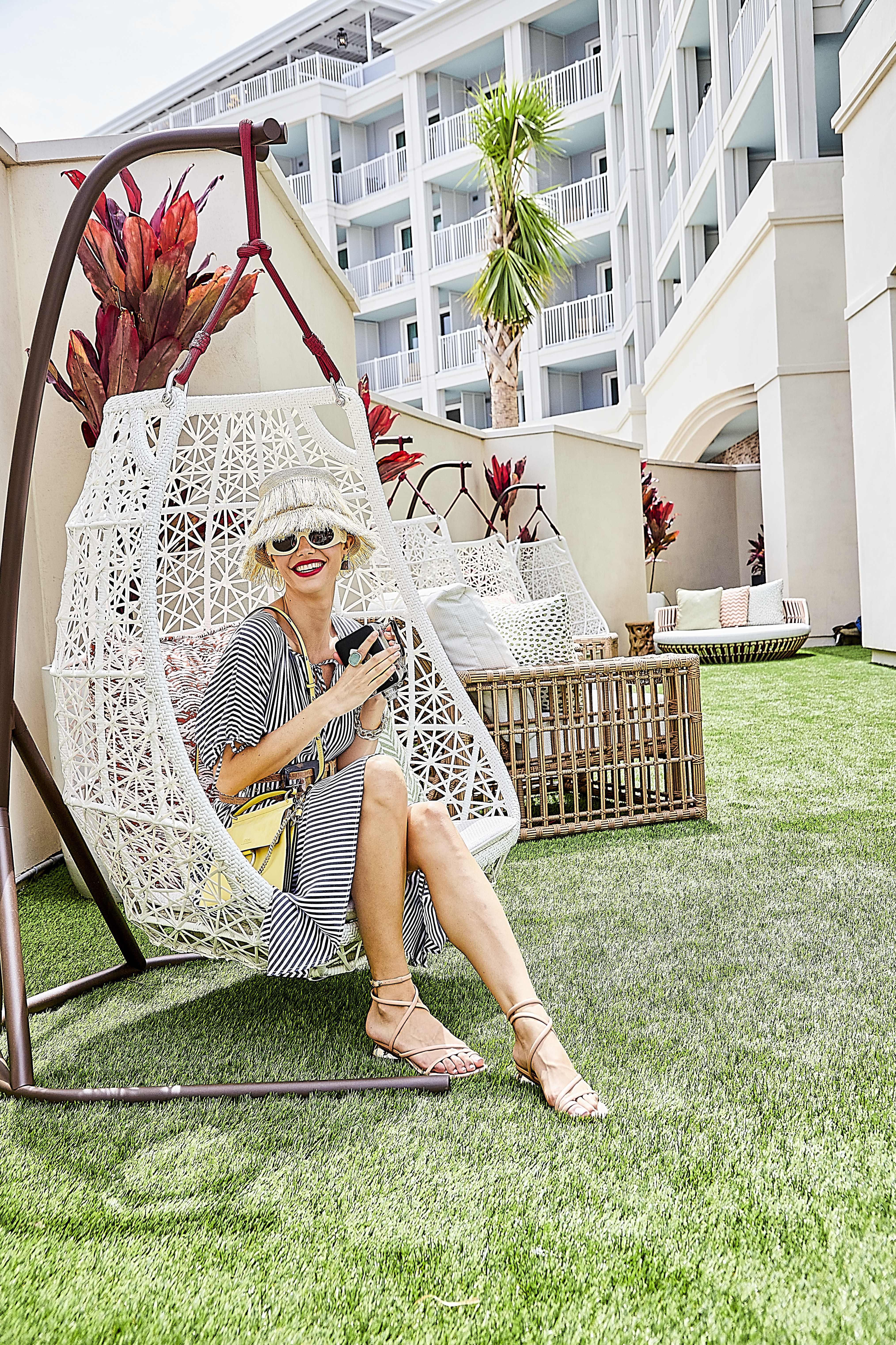 """In a Snap: Peserico striped poplin shirt, $392 at Peserico at The Shops at Belmond Charleston Place; Gucci sunglasses, $1,740, and Nicholas Kirkwood """"Beya"""" sandal, $595, both at Gwynn's of Mount Pleasant; Sensi Studio frayed lamp shade hat, $195, and Staud croc-effect leather-trimmed belt, $50, both at Harper and Hartford; Roberto Coin """"Princess Flower"""" hoop earrings, $4,200 at M.P. Demetre Jewelers;  Chloe """"Faye"""" bag, $1,750 at RTW; gold bangle, $1,650, gold link bracelet; $1,650; gold bangle, $2,540, aquamarine and diamond ring, $3,960, and 47-carat aquamarine and diamond ring, $5,275, all at Croghan's Jewel Box; camera courtesy of Terrace Oaks Antiques"""