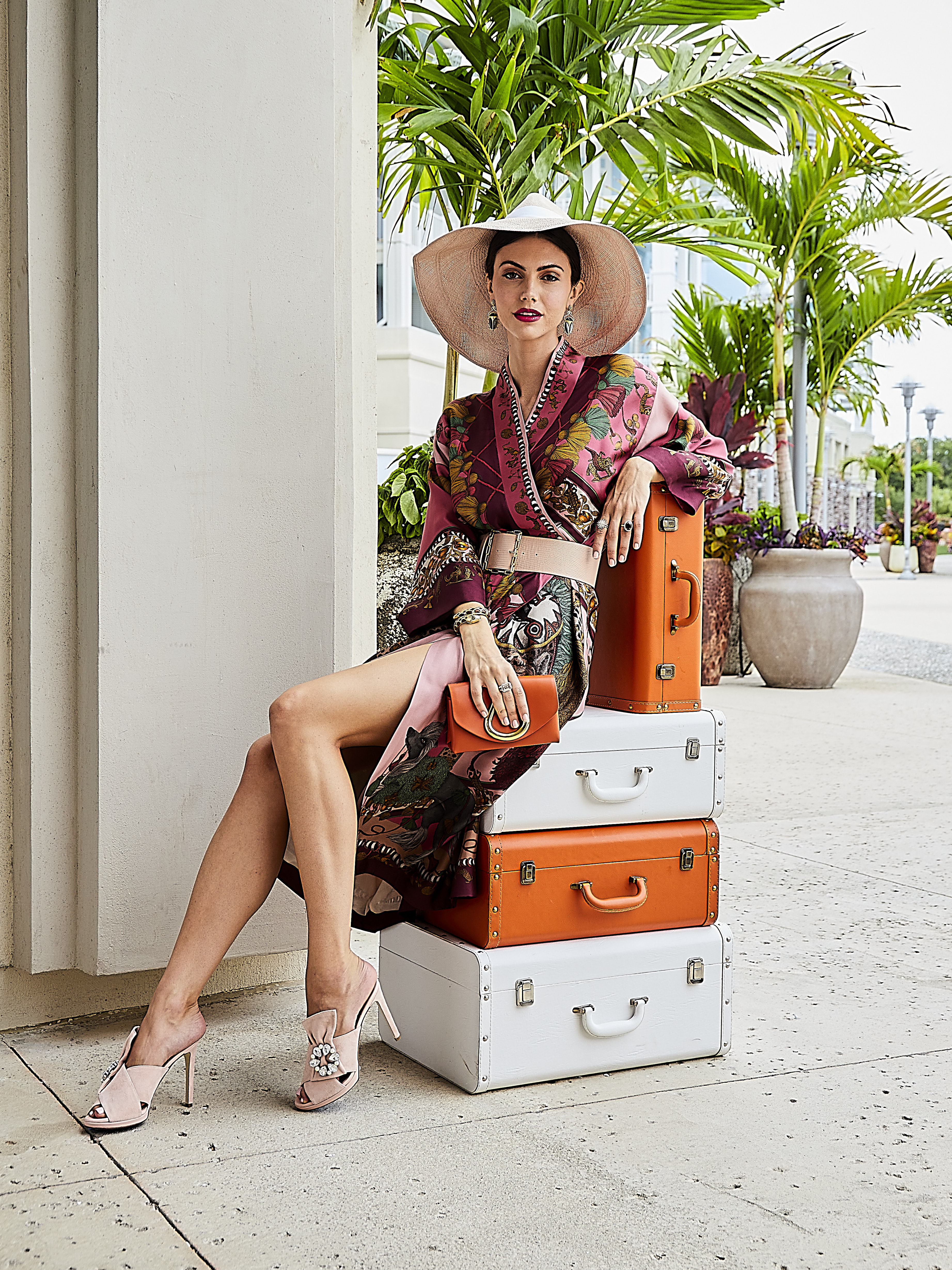 """Jet Set Chic: Sabina Savage kimono-style robe, $1,545 at RTW; Lafayette 148 NY """"Icon"""" hat, $398, Capucine de Wulf """"Scarab Night Berry"""" earrings, $225, and """"Serpentina"""" hinged bangle, $335, all at Gwynn's of Mount Pleasant; Lizzie Fortunato vintage belt, $150 at Harper and Hartford; David Yurman """"Starburst"""" ring, $4,800, and """"Novella"""" statement ring with morganite, $2,900, both at REEDS Jewelers; one-of-a-kind alexandrite ring, $25,000 at Diamonds Direct; St. John mini loop leather clutch, $1,095 at St. John Boutique; """"Kaia"""" blade vamp, $314 at Tara Grinna; luggage courtesy of Harper  and Hartford"""