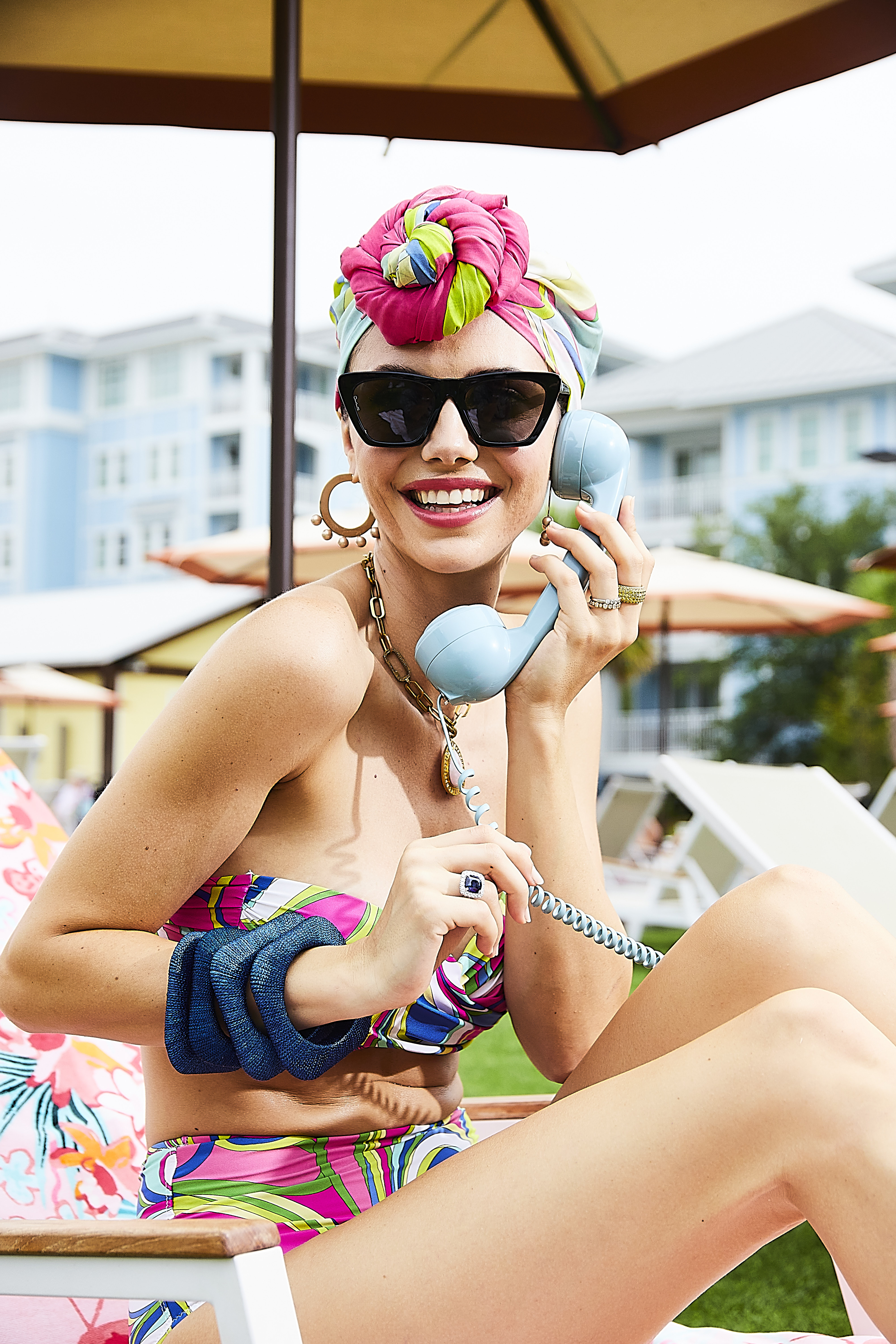 """Social Call: Twist-front bandeau, $94, high-waist bottom, $75, and short kaftan (worn as head scarf), $179, all in the """"Atrani""""print at Tara Grinna; Otra Eyewear """"Step Ahead"""" sunglasses, $60 at Rhodes Boutique; Alexis Bittar pearl-studded hoop earrings, $108, The Woods Fine Jewelry brass chain, price upon request, and pink and opal diamond pendant, $770, and Candy Shop Vintage blue-thread bangles, $48 each, all at Gwynn's of Mount Pleasant; Hearts on Fire bezel diamond band, $2,500 at Sandler's Diamonds & Time; yellow sapphire eternity band, $4,900, and sapphire and diamond cocktail ring, $19,000, both at Diamonds Direct; Spartina 449 """"Pink Lemonade"""" beach towel, $33 at Spartina 449"""