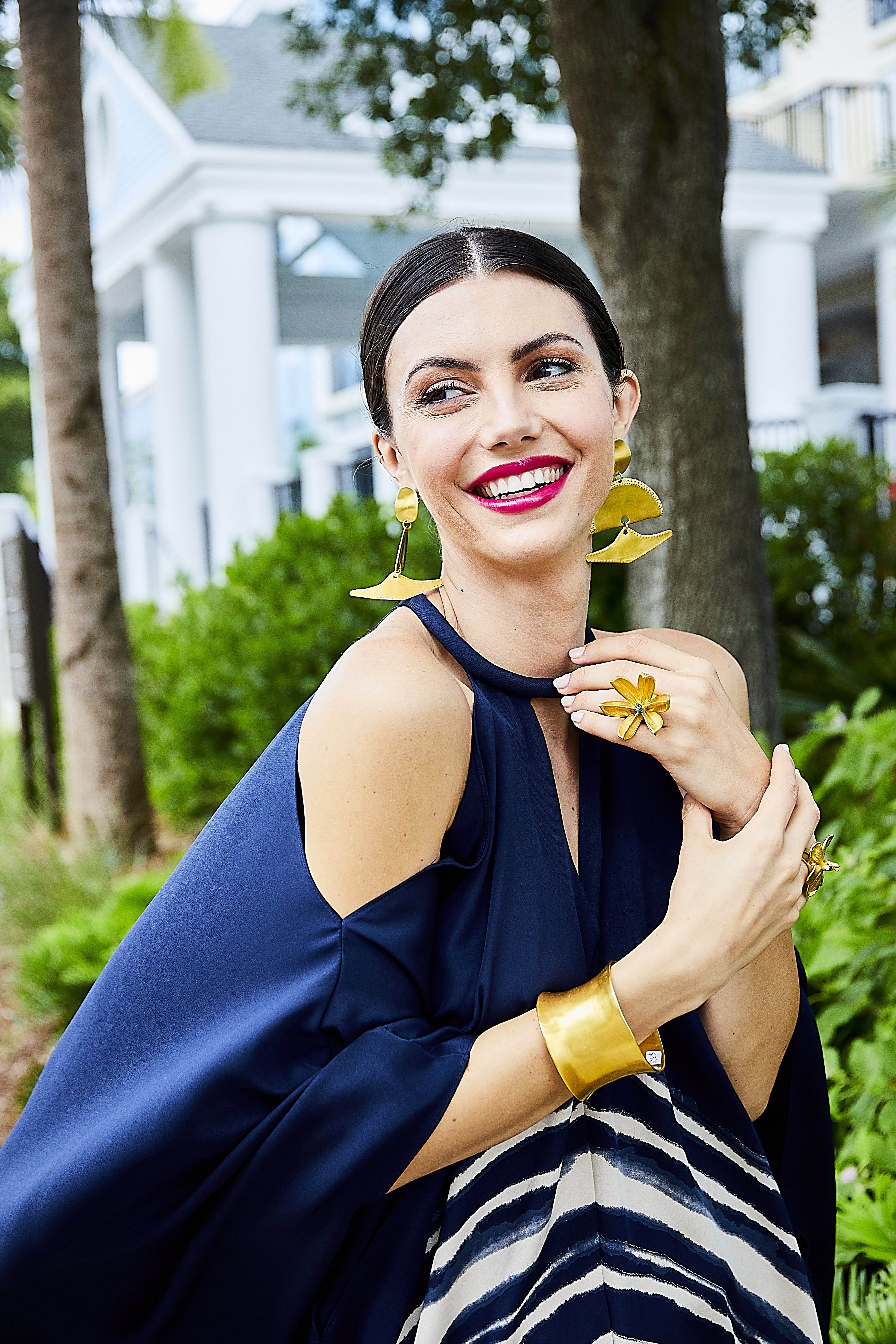 """Flower Power: St. John """"Brushstroke"""" printed silk crepe kaftan, $2,795 at St. John Boutique at the Shops at Belmond Charleston Place;  """"Baudo"""" earrings, $330, Amazonian wide brass cuff, $395, gold flower ring with stone, $340, and emerald orchid ring, $340, all at Ibu"""