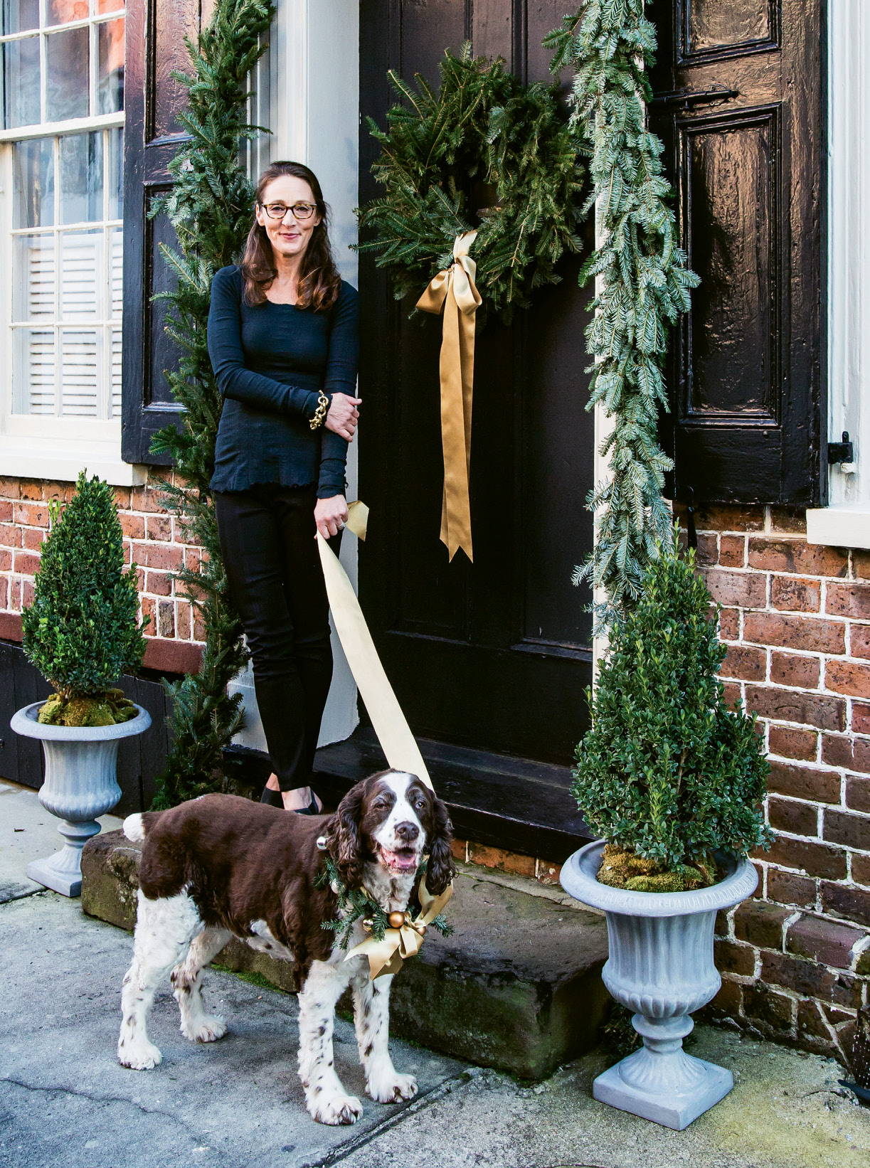 WELCOME HOME: Tara and her English springer spaniel, Georgia, greet guests as they arrive to their Tradd Street home.