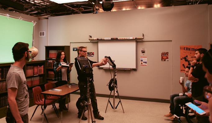 """Bryan Curb (center) directs a shot inside """"Jamestown University."""""""