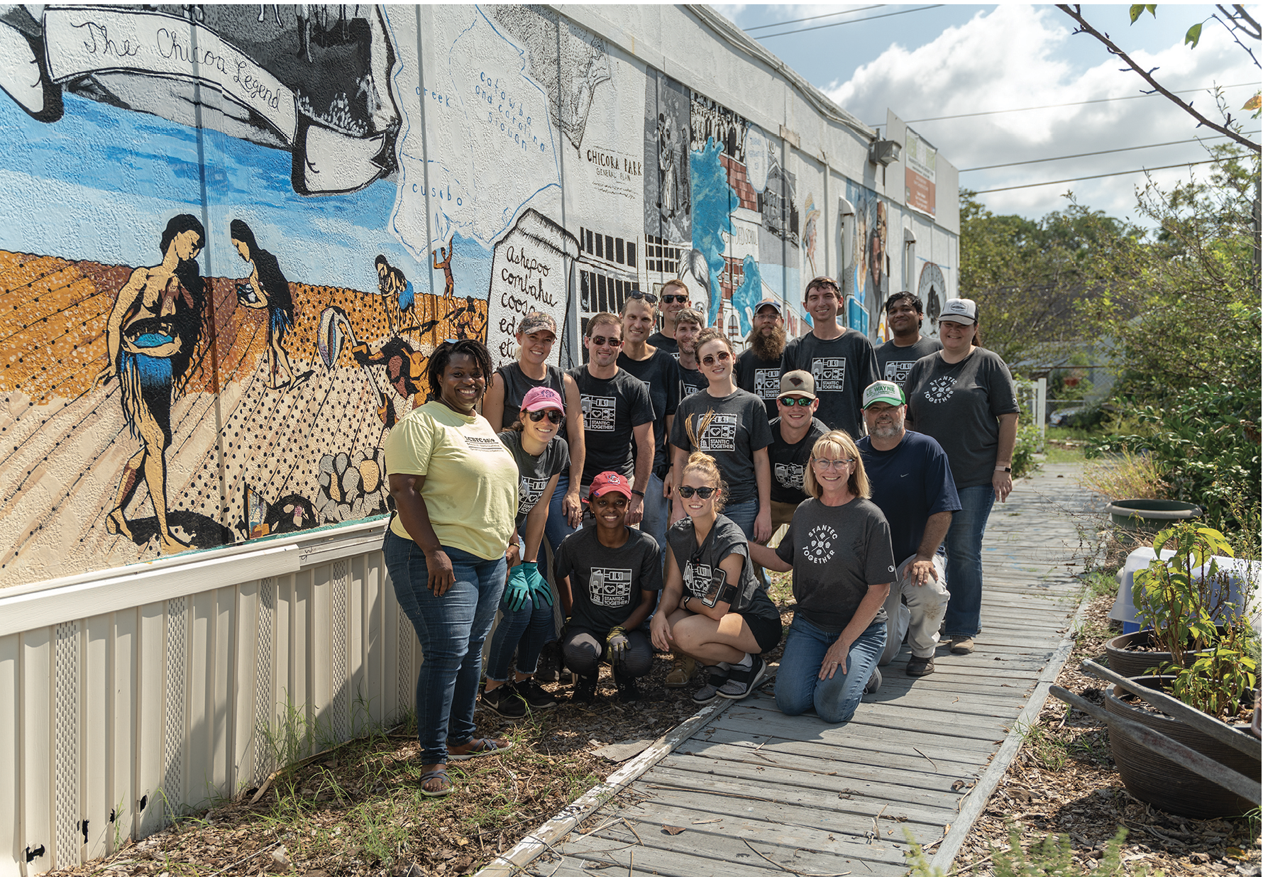 All Hands on Deck: The farm's core team gets lots of help from volunteers, such as these employees from Stantec, pictured with Jenkins next to the farm store. The mural, which special projects manager Anik Hall researched, organized, and painted, depicts 500 years of the Chicora-Cherokee neighborhood's history.