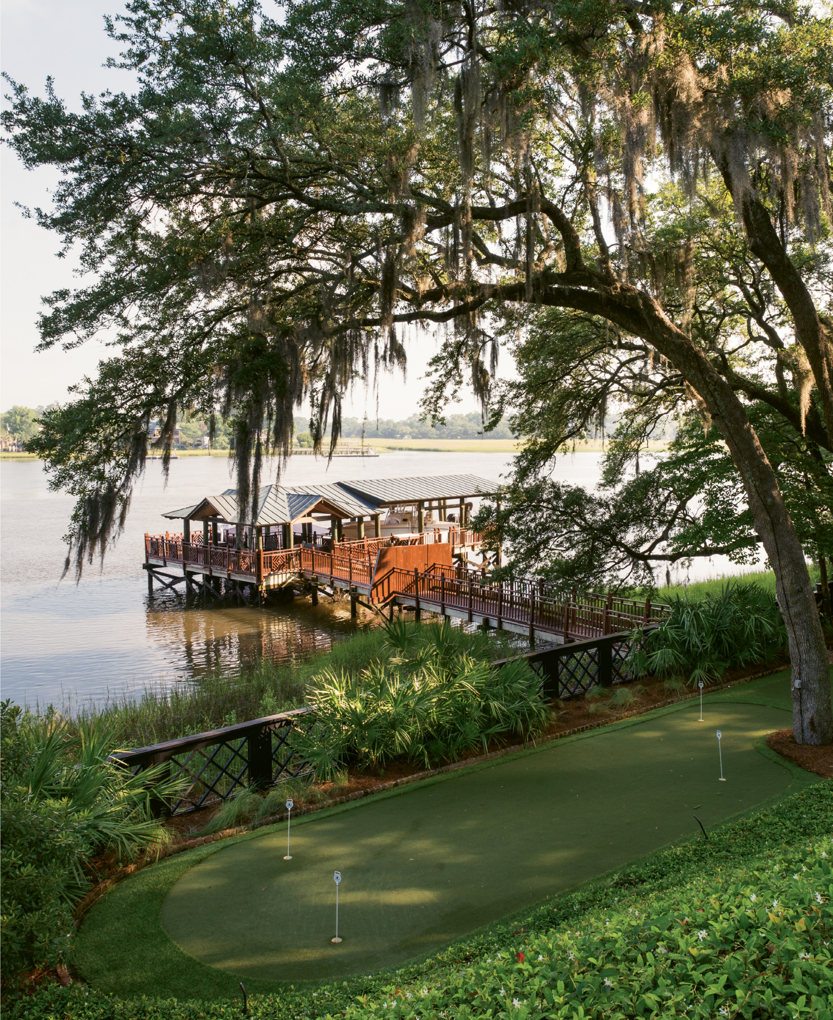 Ground Strokes: Wertimer's landscaping cascades down to the putting green and dock with a boathouse.