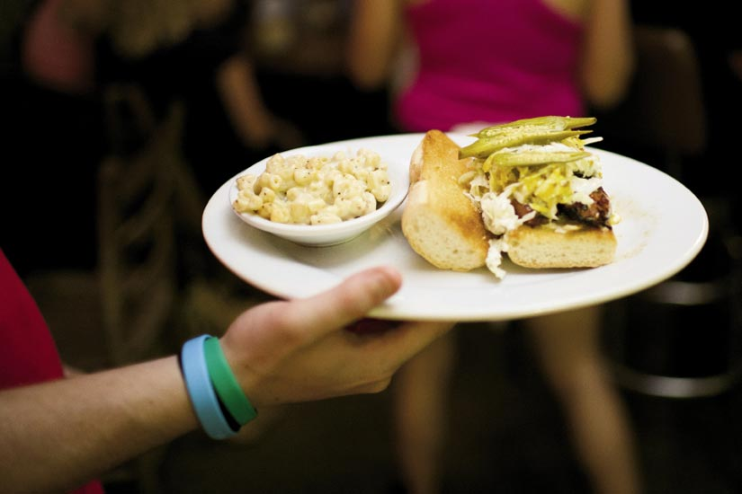 Home Team BBQ offers a smoked sausage sandwich with pickled okra and mac-n-cheese on the side