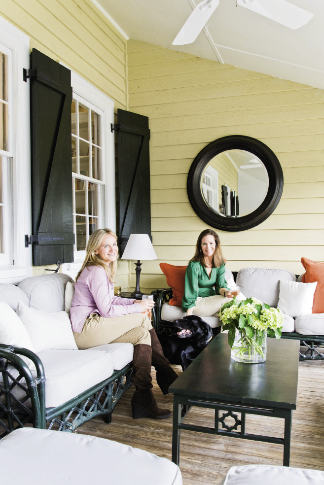 "Color Scheme: Nathalie (left) and Jenny relax on the front porch, where they reused Jenny's outdoor furniture from her old house and simply added orange accent pillows from Carolina Pottery to freshen it up. ""When I bought the house, the shutters were bright turquoise,"" says Jenny. ""We painted them Charleston Green, which is more my style."""