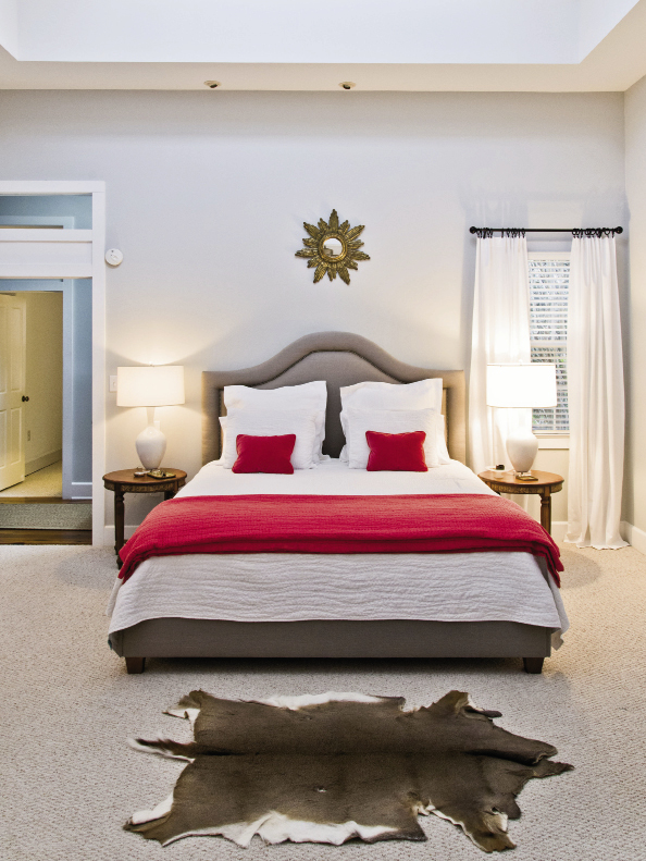 The master bedroom, furnished with a pair of lamps from Celadon, a deerskin rug from the boys' hunting collection, and an upholstered khaki headboard from GDC.