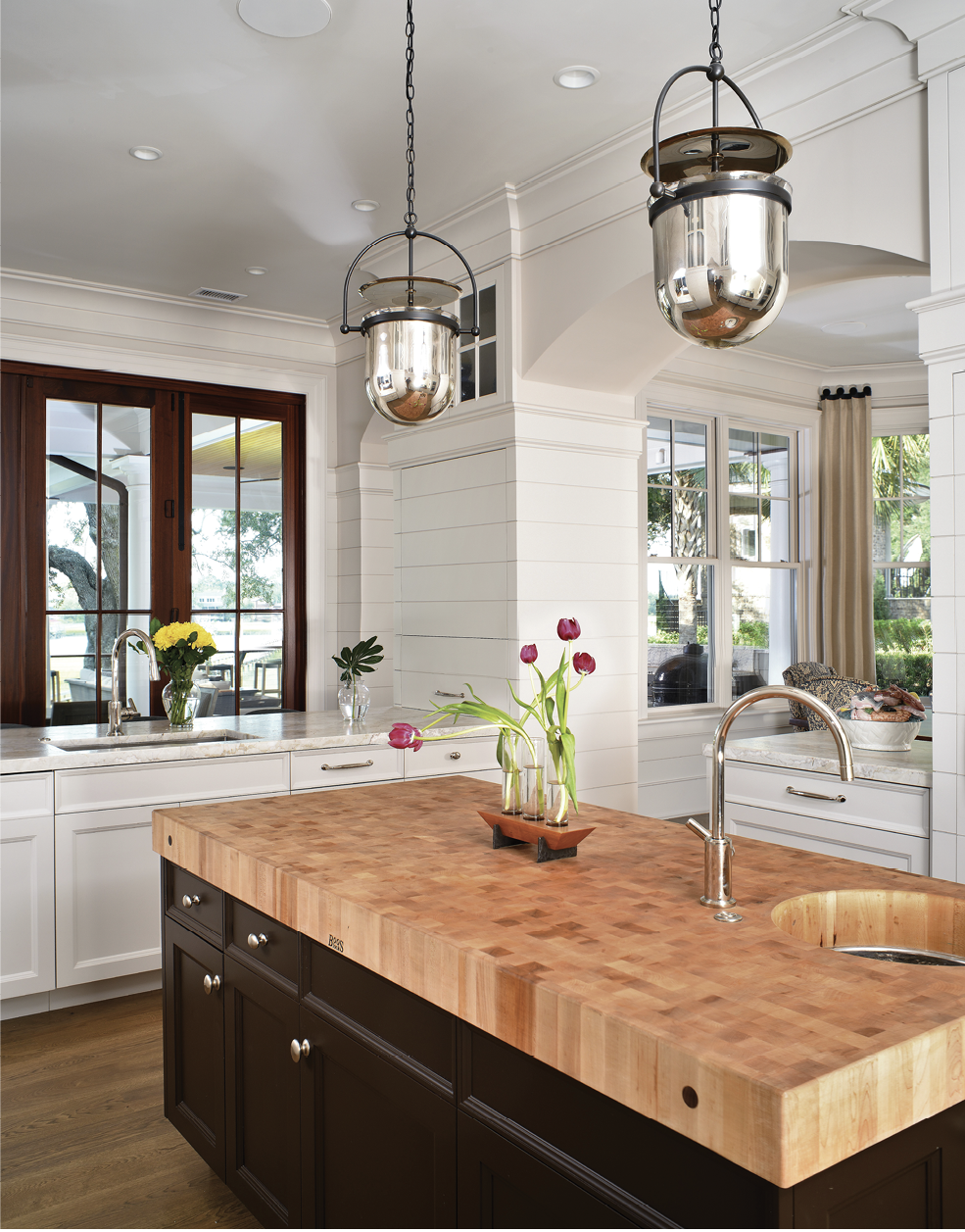 The kitchen features a Boos Block island and industrial-style pendant lights from Urban Electric.