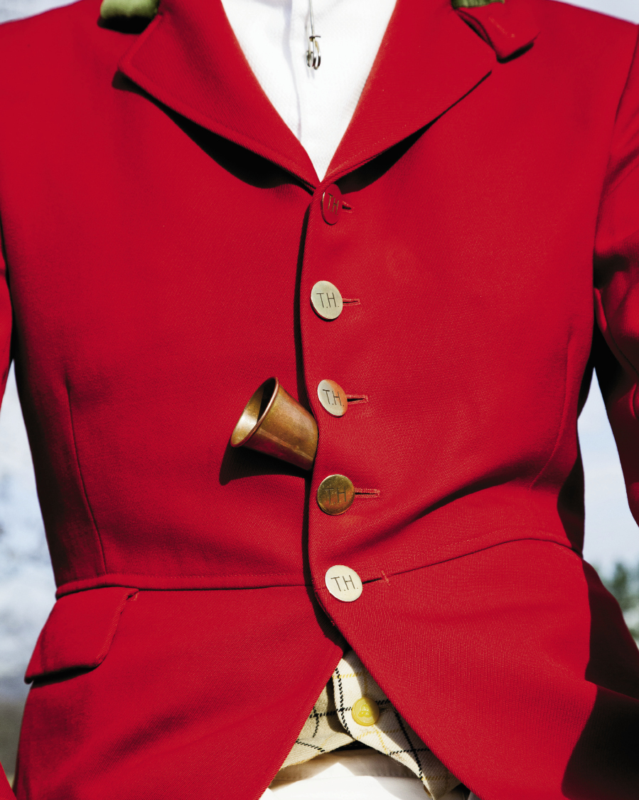 Huntsman Jordan Hicks sports a scarlet coat with buttons engraved with Tryon Hounds' initials and uses an English-made horn to call to the yelping pack.