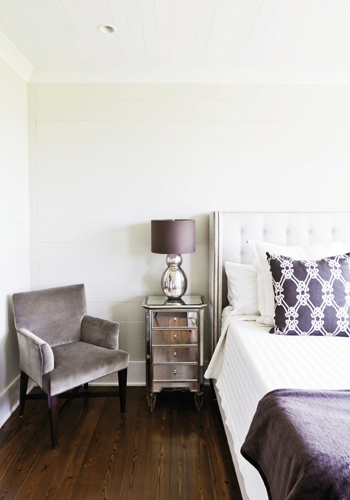 Luxe is More: The master bedroom is outfitted simply with an upholstered bed, mirrored nightstand, and a sable-toned velvet armchair.