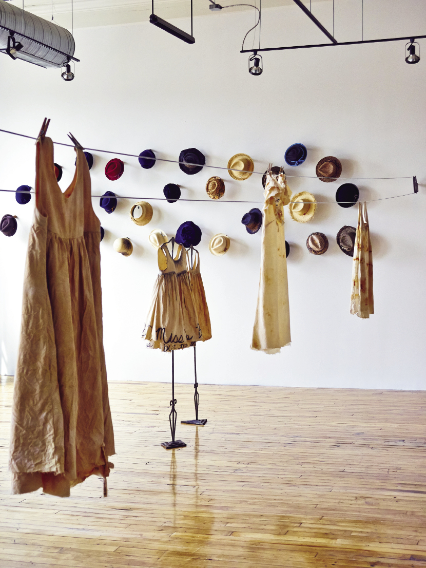 At the 701 Center for Contemporary Art, the new Madame Magar collection of muslin and canvas frocks hangs on pulleys and  hooks. As part of the exhibit, Charleston-based designer Leigh Magar has created a temporary studio workshop within the gallery space so  visitors can see her sewing, dyeing, and adding penciled lettering to the dresses.