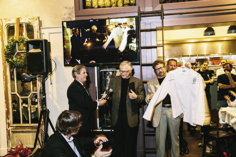 "Maverick Southern Kitchens partners David Marconi and Dick Elliott present Lee with a chef's coat ""signed by so many wonderful people and I can't ever wear it or wash it,"" he says."
