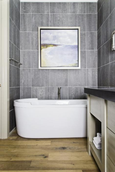 Spa Treatment: Gray slate tiles run floor to ceiling and offer a serene backdrop for deep spa tubs in both master baths.