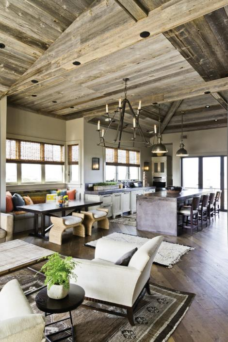 Up In The Air: A rustic, barnwood ceiling and antique Oushak and Moroccan rugs offset the kitchen's cool, industrial sensibility, defined by a concrete island and countertops and Visual Comfort pendant lighting.