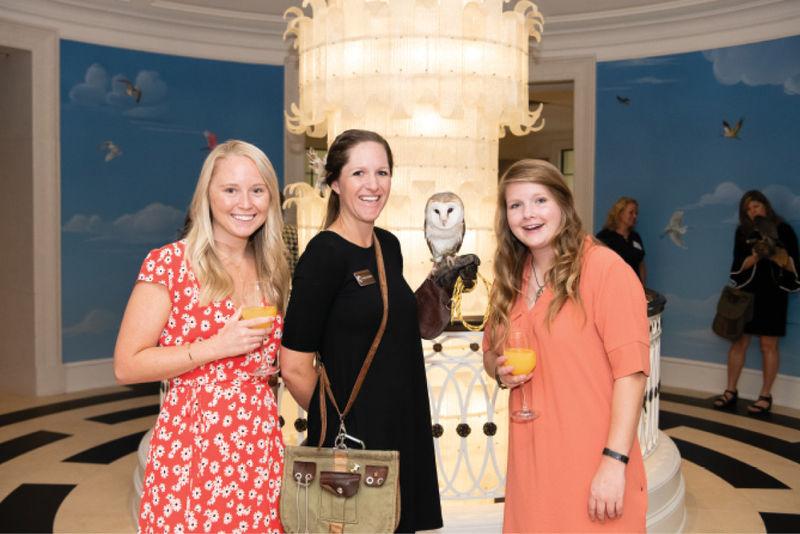 Kelsey Johnson, eductator Natalie Hendrickson holding a barn owl, and Brittany Freeman