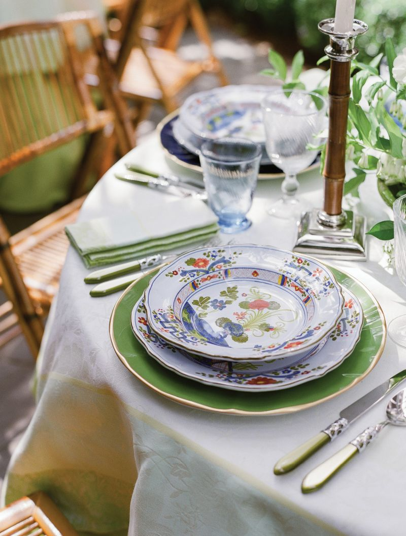 """Each place setting pairs the Italian plates and bowls she and Dean selected when they were first married with bright chargers and Vietri utensils. """"We have beautiful family silver that we use for more traditional dinners,"""" says Lynn, """"but the colorful cutlery just says, 'Fun!''"""