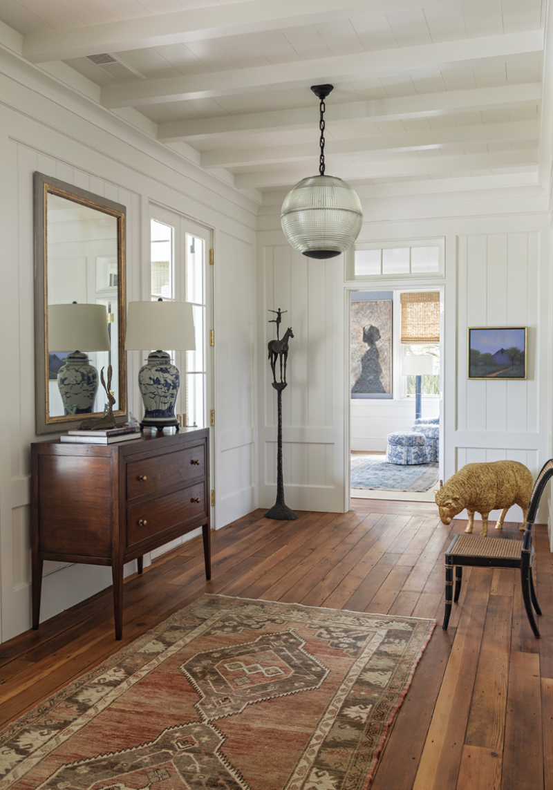 The large foyer provides an ideal space to showcase some of the couple's sculptures, including  the bronze Horse and Rider II by Tom Corbin. A spectacular pair of Parisian street lamps repurposed into chandeliers hang in front of matching Holland MacRae Carlton chests. The layering of art and vintage rugs with blue and white porcelain lamps creates an inviting entrance.
