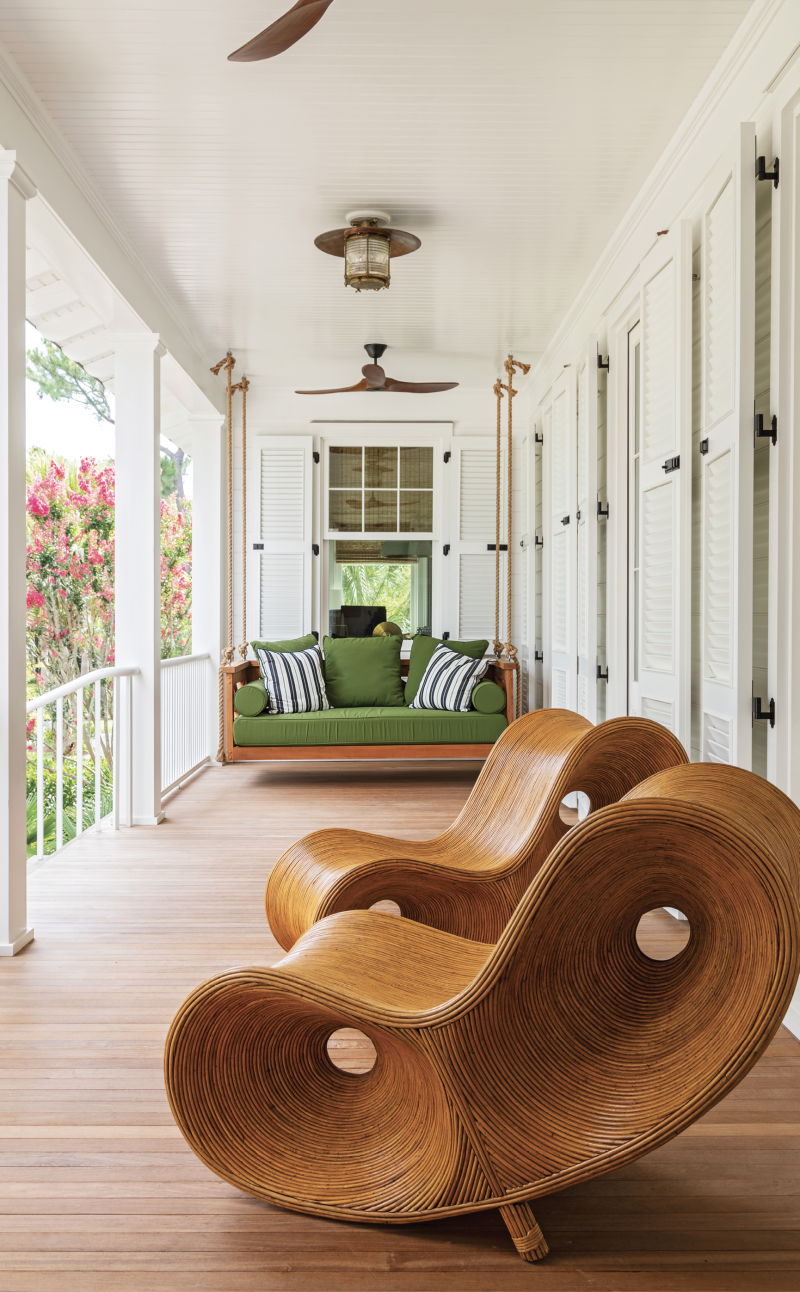 """A swing is a must for a Lowcountry porch, and this one, covered in Sunbrella """"Palm"""" canvas at the front entrance hints to the green and blue hues inside. The Rattan Infinity Loungers from Fritz Porter add a playful, artistic touch and the repurposed nautical light fixture brings in the vintage vibe."""