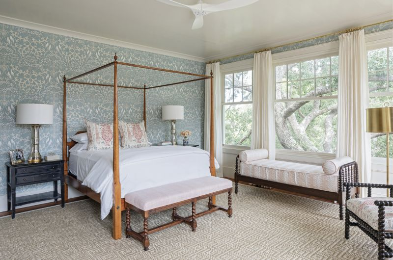 """No art was needed in the owner's bedroom once the architects' expanded the room's east-facing windows to bring in the natural beauty of its live oak neighbor. Dufford Young also removed smaller windows from the north wall creating the perfect space for the antique four-poster bed, which is accentuated by Penny Morrison """"Vasari""""-wrapped pillows and Lewis & Wood """"Bella"""" wallpaper from Fritz Porter."""