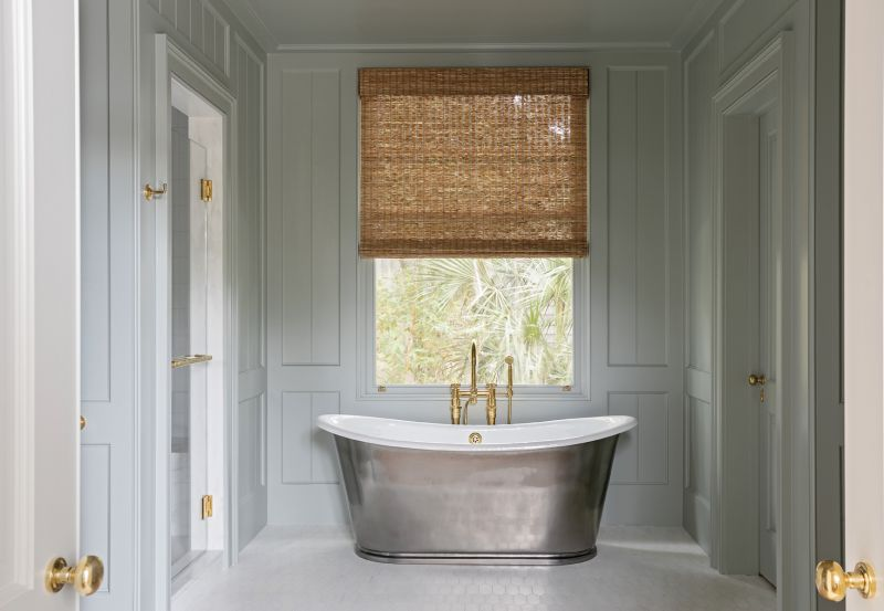 """A freestanding cast iron tub from Waterworks with brass fixtures from Bird Hardware is a centerpiece in the panelled room painted in Farrow & Ball """"Light Blue."""""""