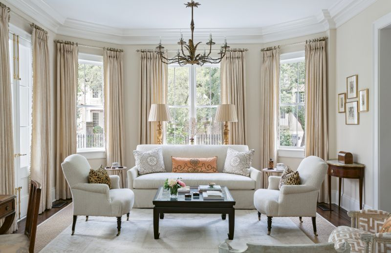 QUIET ELEGANCE: Cream walls with cream damask curtains and neutral upholstery create a timeless background in this large living room. Pillows of leopard velvet, Fortuny damask, and melon velvet with vintage trim add texture and color, while Spanish Barcelona gilt tole chandeliers from David Skinner Antiques provide playful whimsy.