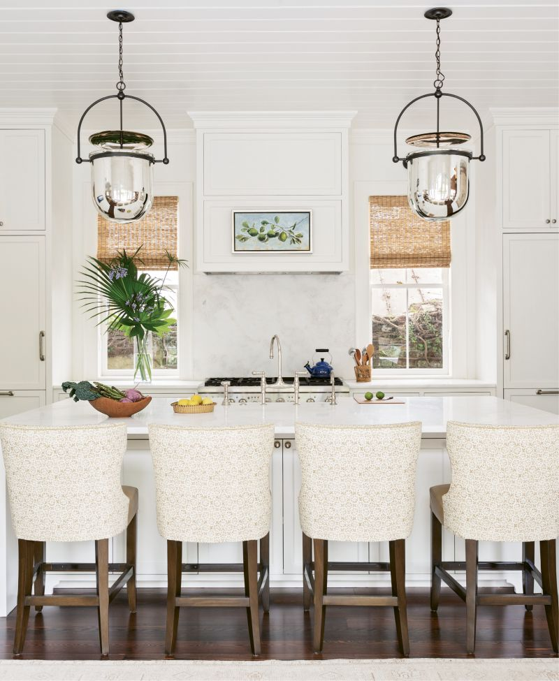 """SIMPLE SYMMETRY: Dominated by a large white Namib marble-topped island, ideal for gathering the family as well as spreading out the newspaper, the kitchen is literally and figuratively the heart of this home. A pair of """"Urban Smokebell"""" lanterns from Urban Electric add a grand scale and align perfectly with the two newly discovered windows, previously covered by cabinets."""