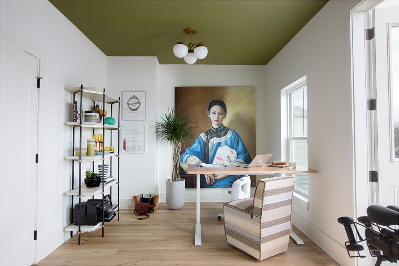 A large portrait found at a vintage market dominates Vickers's office/home gym. She pulled in a deep green hue from the painting for the dramatic ceiling.