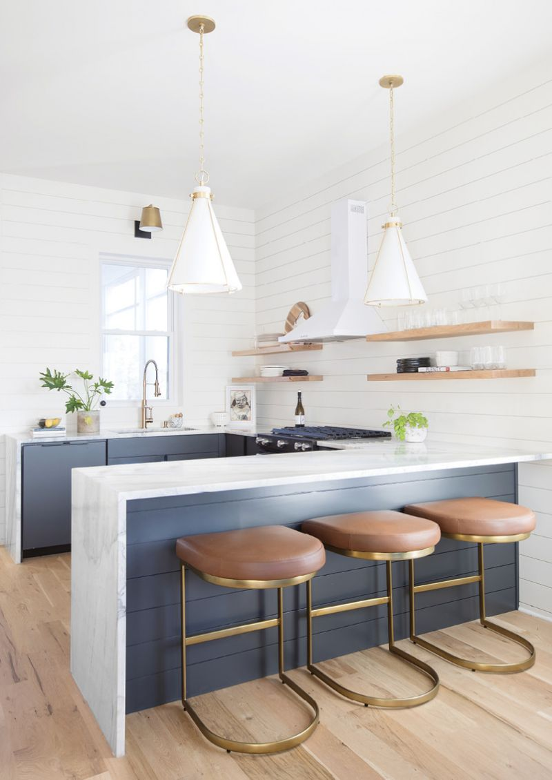 LUXE DETAILS: Rio Venato marble countertops that waterfall to white oak flooring provide a high-end focal point, contrasting beautifully with the dark cabinetry and Alder and Tweed leather and bronze stools. A pair of Hudson Valley pendant lights complete the modern, organic look.