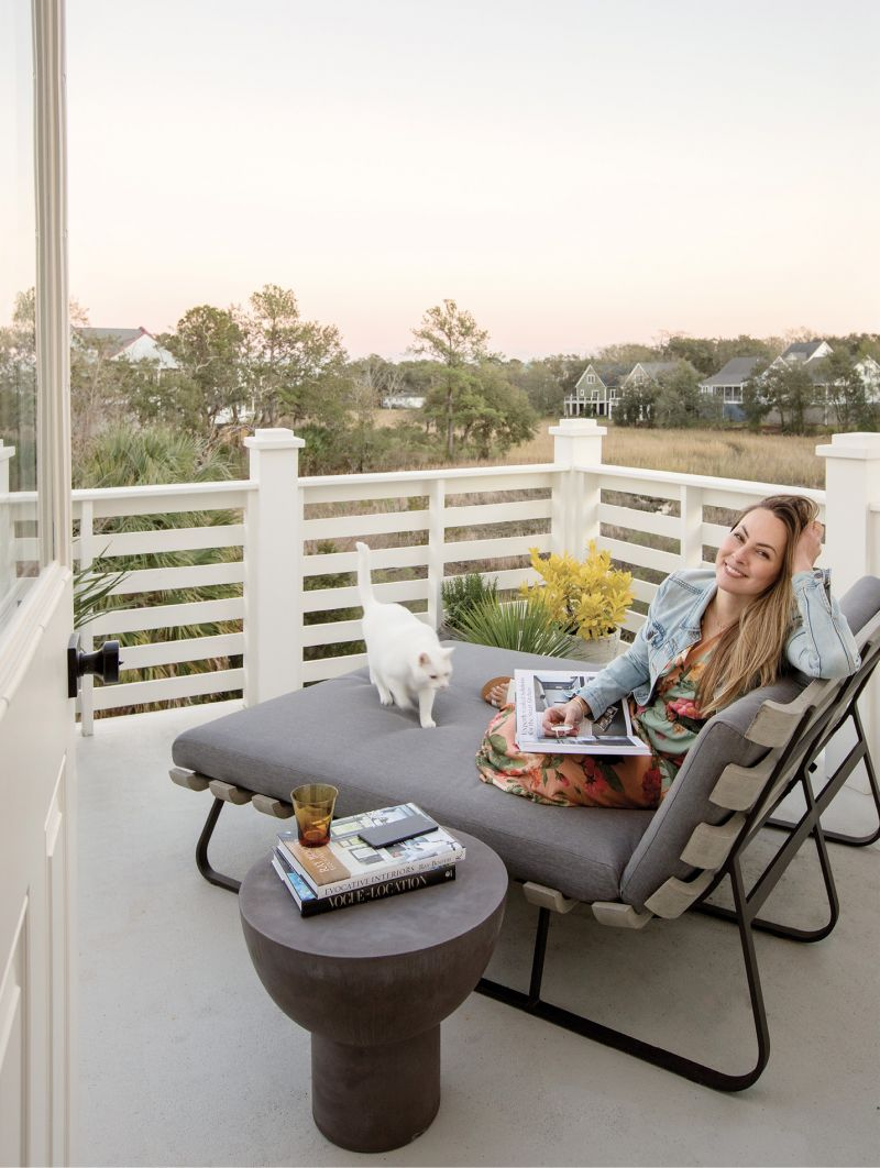 SEEKING SERENITY: It was the marsh view that drew Jesse Leigh Vickers to this North Charleston gem, and the top floor porch, outfitted with a double chaise by Four Hands and table by CB2, is the perfect place to read, relax, and soak up the scenery with her cuddly cat, Pickles.