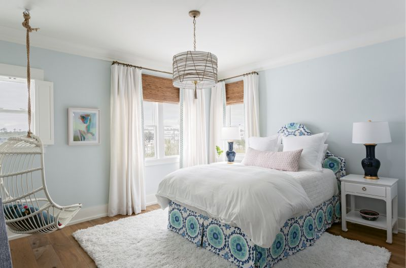 """The McElveens' youngest daughter's bedroom boasts eye-catching fabrics, from the custom-made bench in the Galbraith & Paul """"Seville Tile"""" print in the master to the linen headboard with matching blue Quadrille bed skirt."""