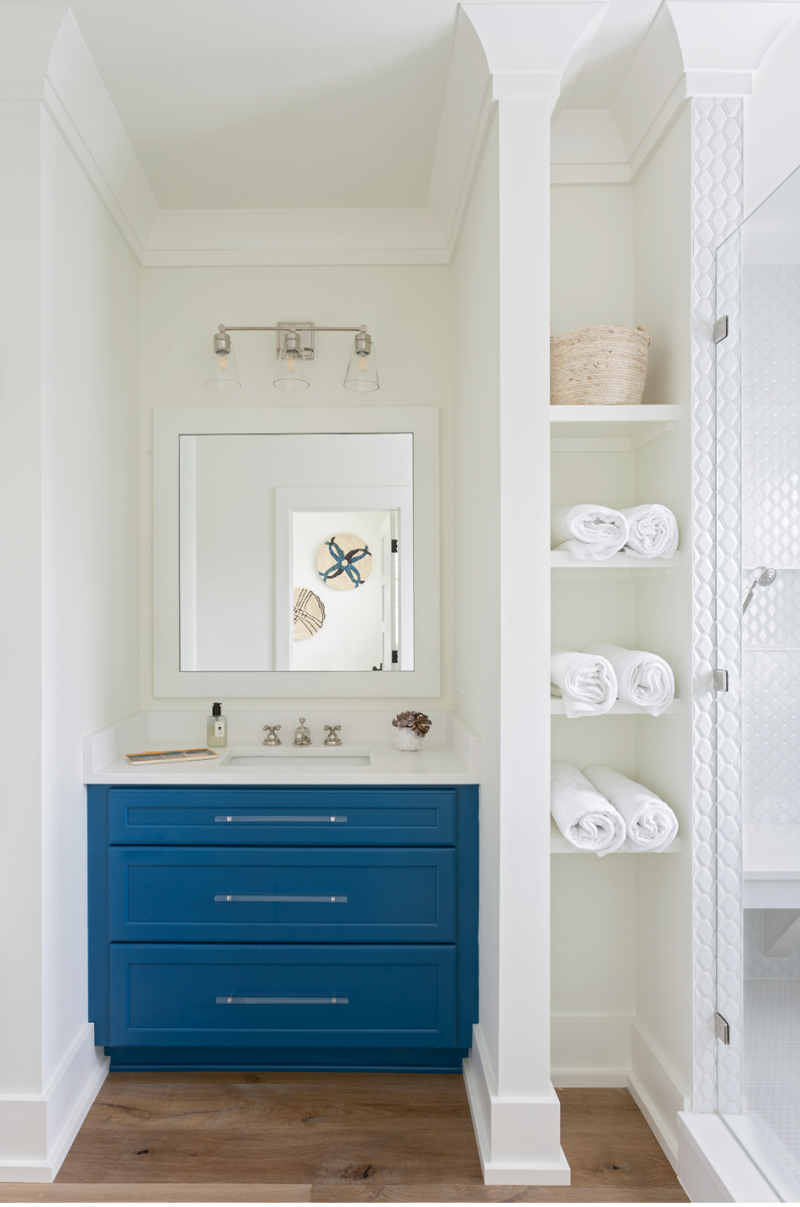"""A Pop of Color: The daughters share this remodeled bathroom, which was redesigned to afford a much larger shower space, complete with a bench and finished in subway tile from Melcer Tile. Custom cabinetry from Spartina Cabinets is offset by the Benjamin Moore """"Simply White"""" wall color and illuminated by a vanity light in polished nickel from Carolina Lanterns."""
