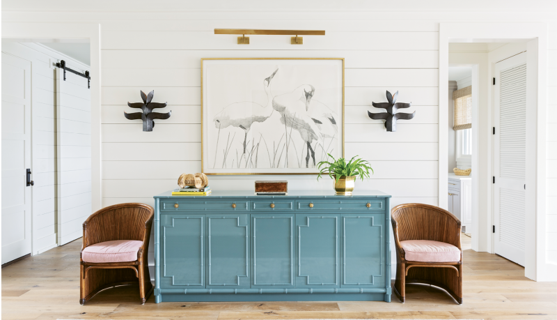 """Perky Pastels: A custom-designed French blue credenza punctuates the McElveens' expansive entryway. Two vintage chairs from Charleston's Indigo Market and a Judith Vivell charcoal drawing, """"Whopping Cranes in Reeds II,"""" finish off the vignette."""