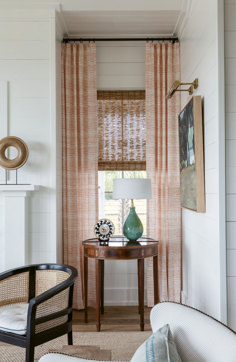 Serene Scene: An antique heirloom demi lune table displays a lamp from Elizabeth Stewart Design; its green hues mimic the lush view. A Mark Sikes caned chair from One Kings Lane sits on a Stark sisal rug, providing a hint of masculinity to the soft palette.