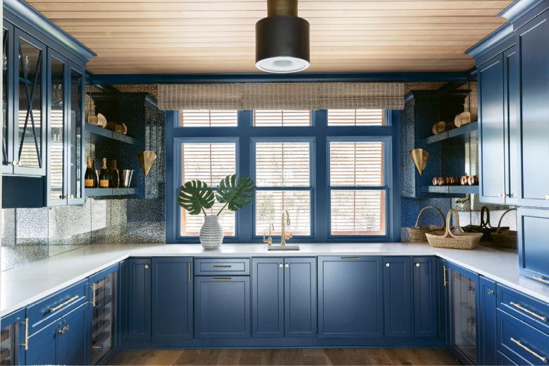 """Painted with Sherwin Williams's brilliant """"Rainstorm"""" and illuminated by the Urban Electric """"Jackson"""" light fixture, the cabinetry by Spartina Kitchens is furnished with custom brass fittings."""