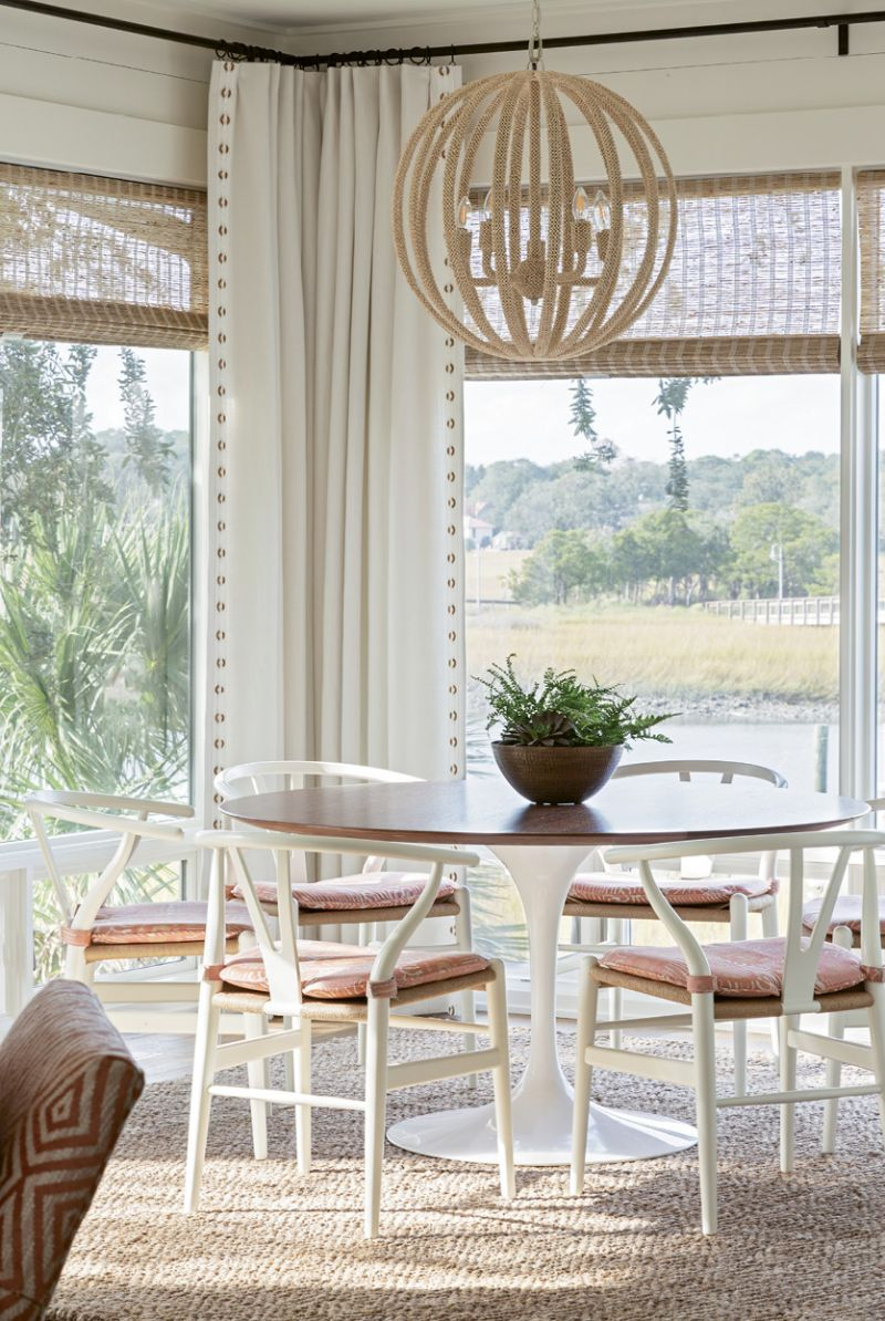 A simple walnut, tulip-based breakfast table, watched over by a coco-bead chandelier from Palecek, offers idyllic views of the creek and the Ravenel Bridge.